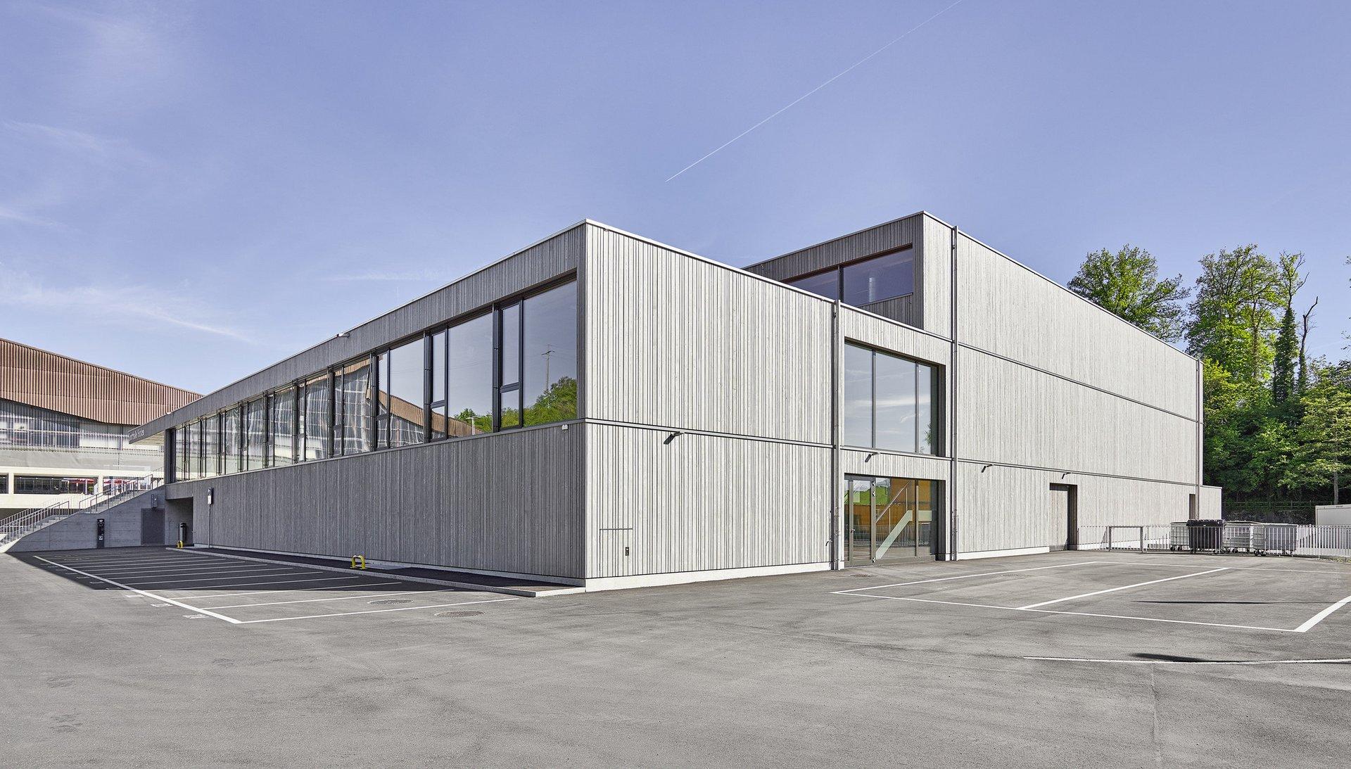 Grande salle de sport, vue extérieure, façade en bois d'épicéa gris