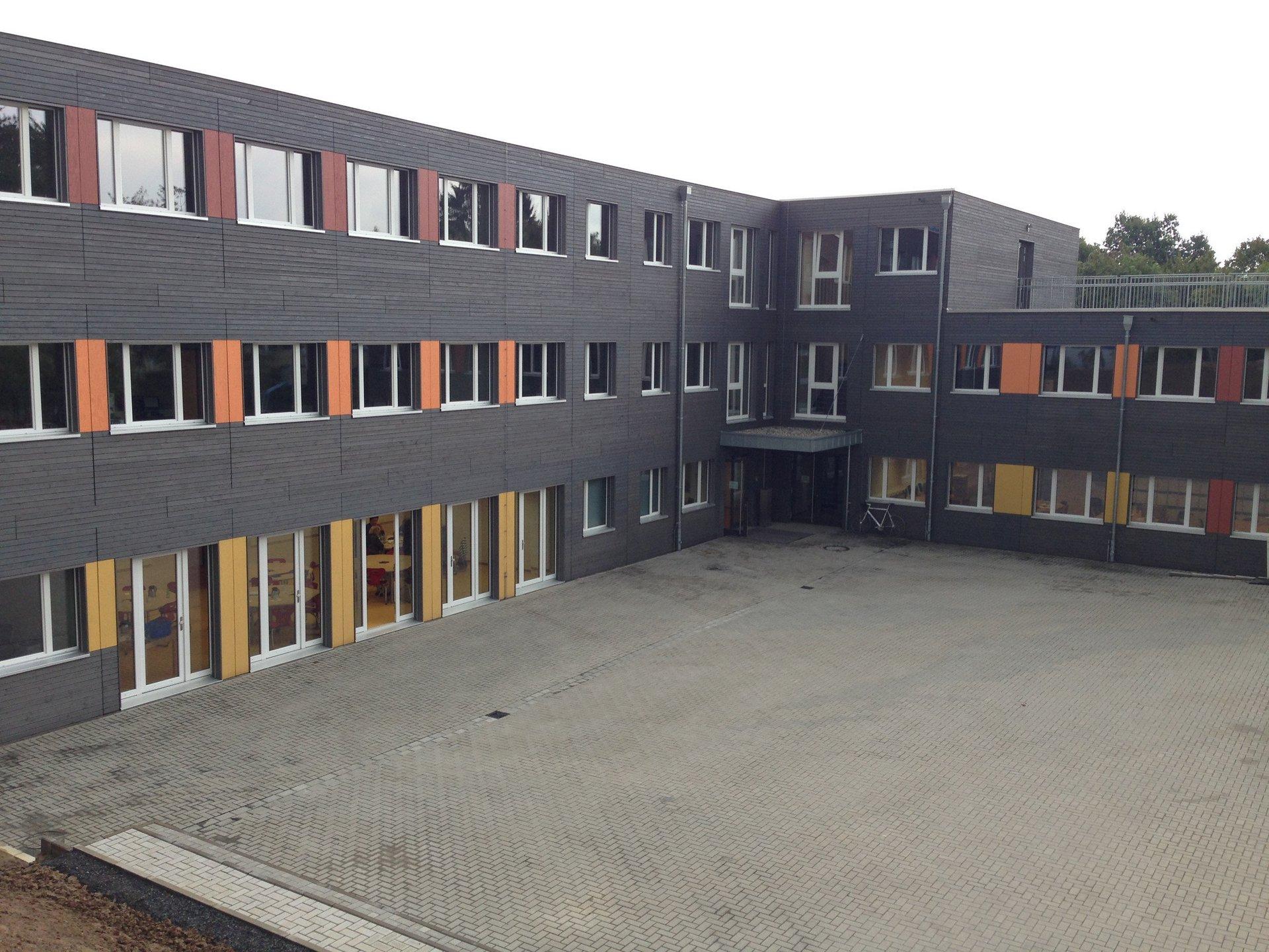 3-geschossiges Schulgebäude mit Schulhof und bunten Fassadenakzenten