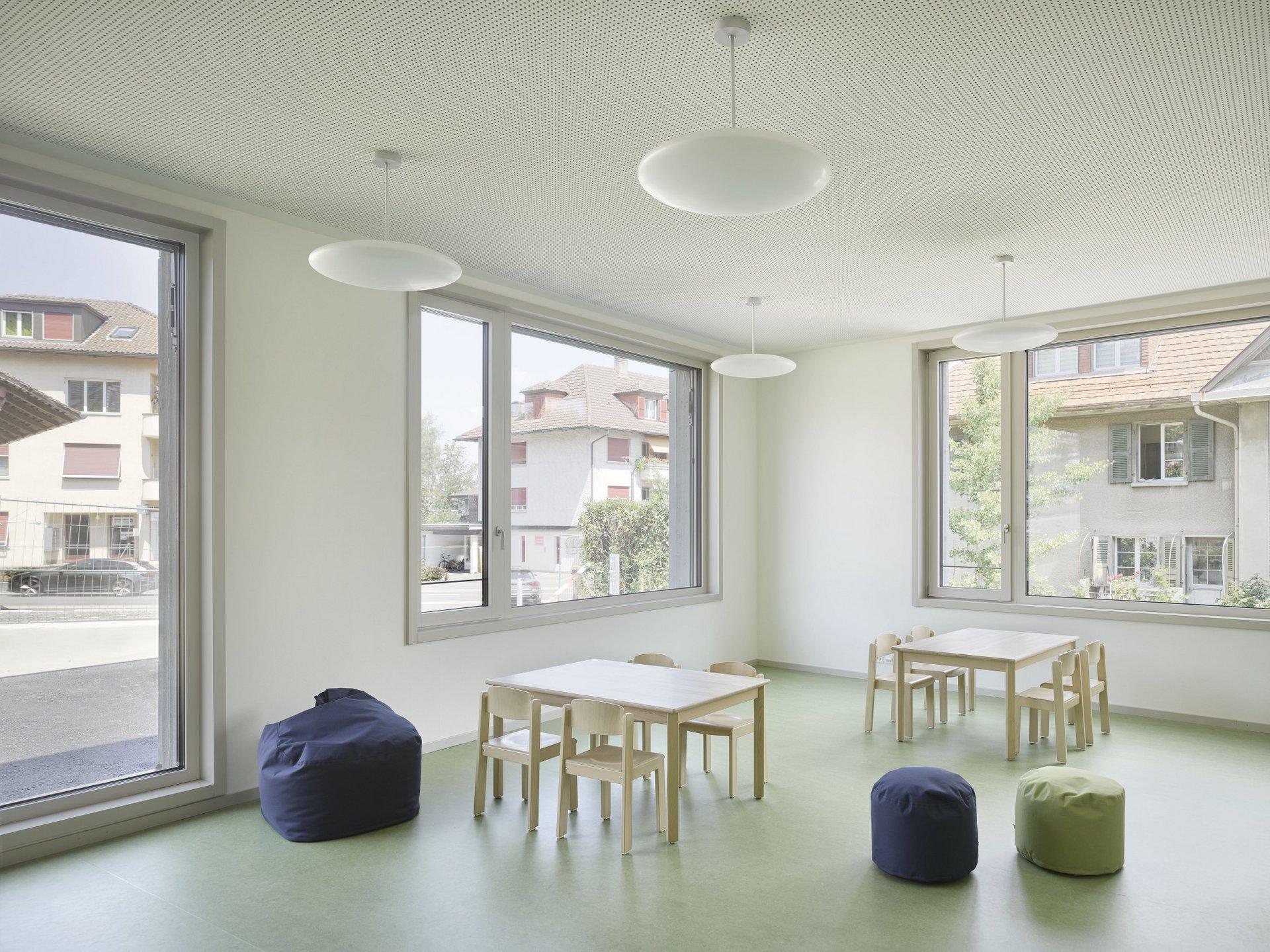 Durch grosse Fenster gut belichteter Innenraum eines Schulzimmers mit Arbeitstischen und Sitzsäcken