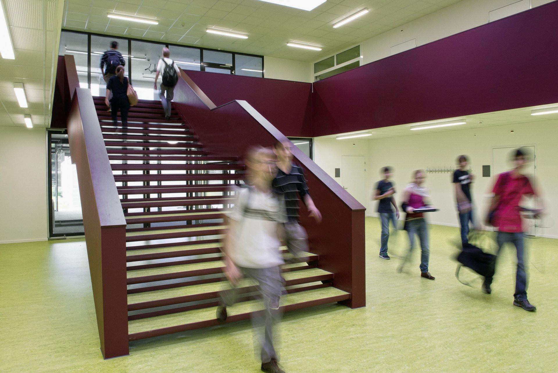 Eingang Schulgebäude mit roter Holztreppe während Schulalltag