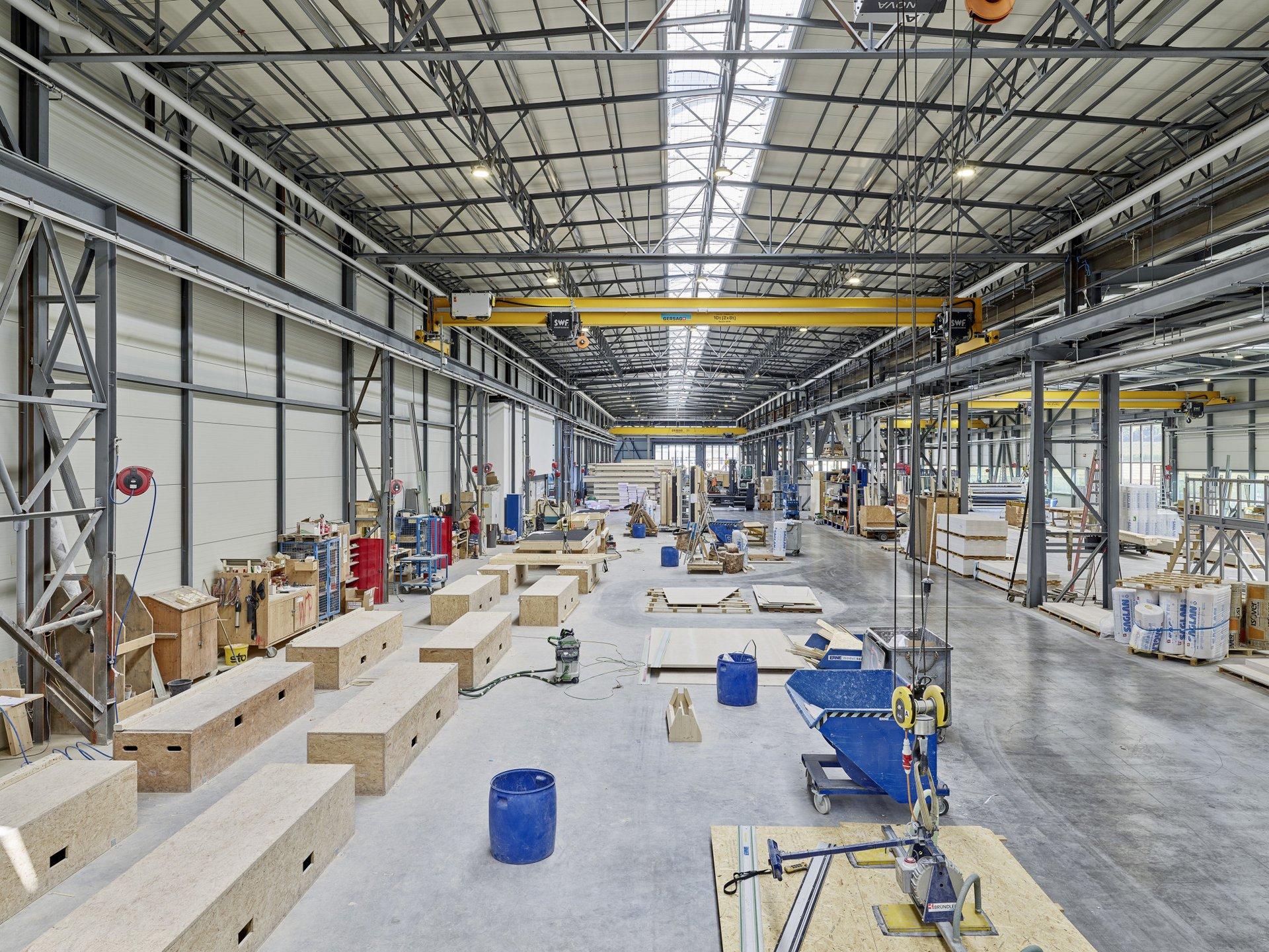 Einblick in die Produktionshalle wo einzelne fertige Elemente zwischen blauen Tonnen und Werkzeugen zur Weiterverarbeitung stehen