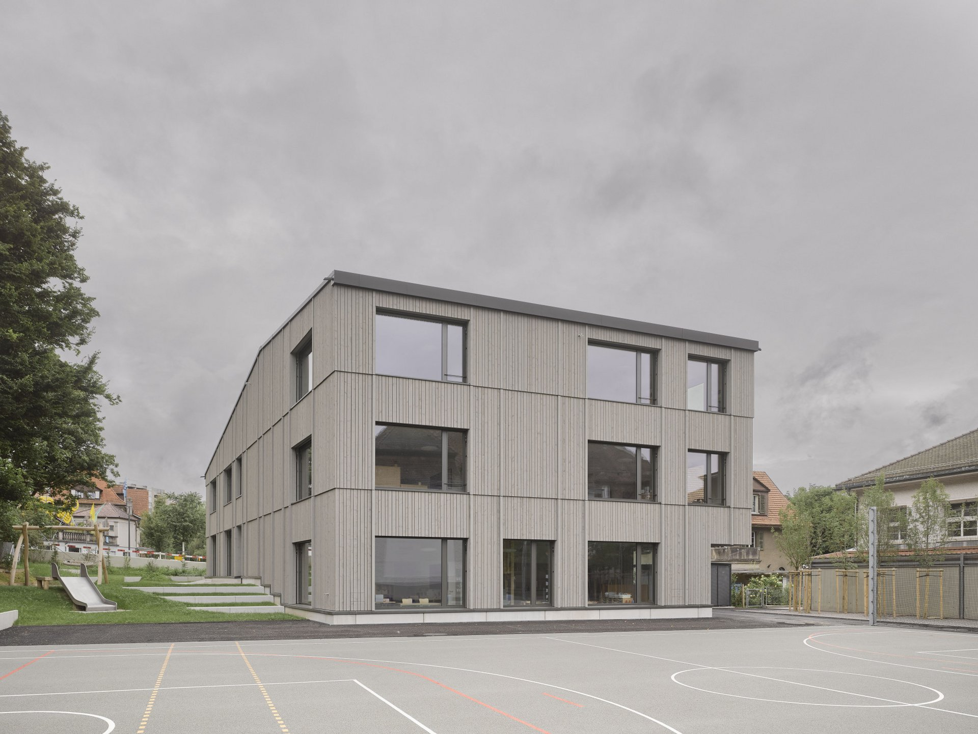 Blick auf die Fassade eines Schulhauses mit vielen grau schimmernden grossen rechteckigen Fenstern