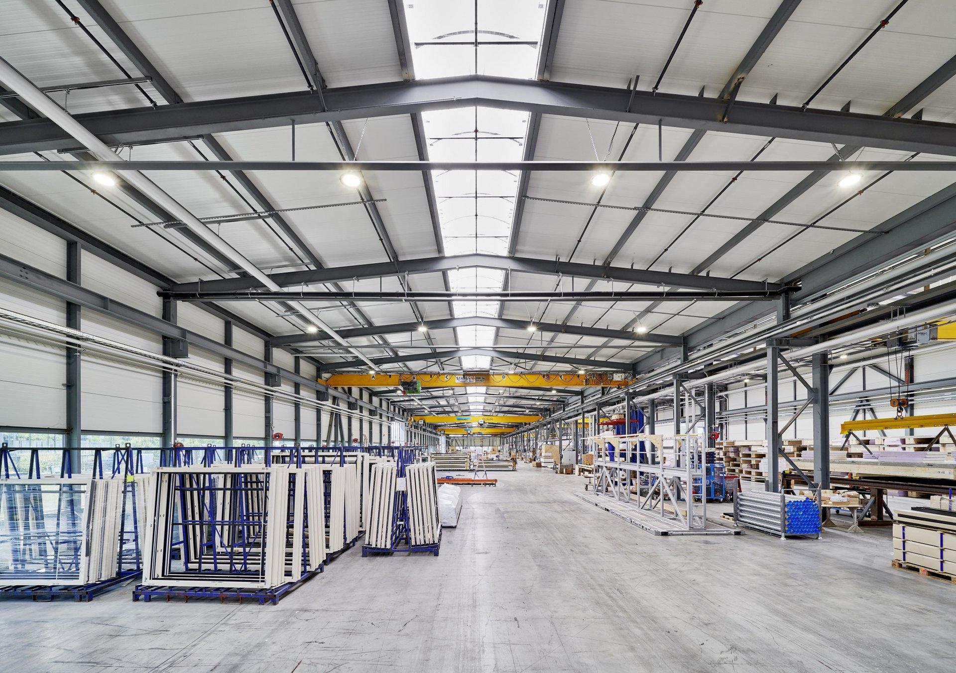 Einblick in das Innere der Produktionshalle und die darin gelagerten weissen Fenstern.
