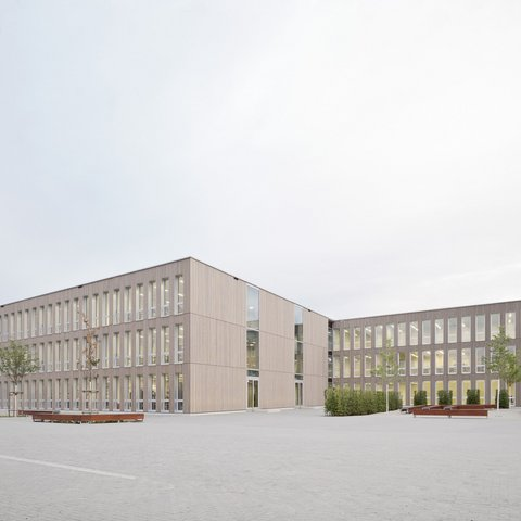3-geschossige temporäre Schule aus 200 Holzmodulen und vertikal angelegten Holz-Metallfenster