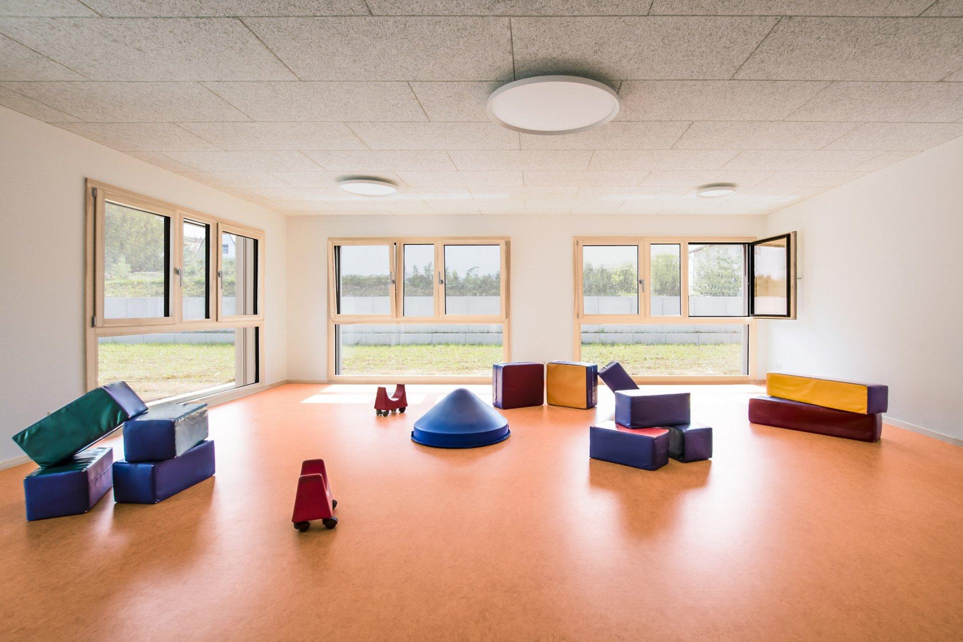 Blick in das Spielzimmer mit drei grossen Holzfenstern, der orangene Boden ist von Spielzeug übersäht.