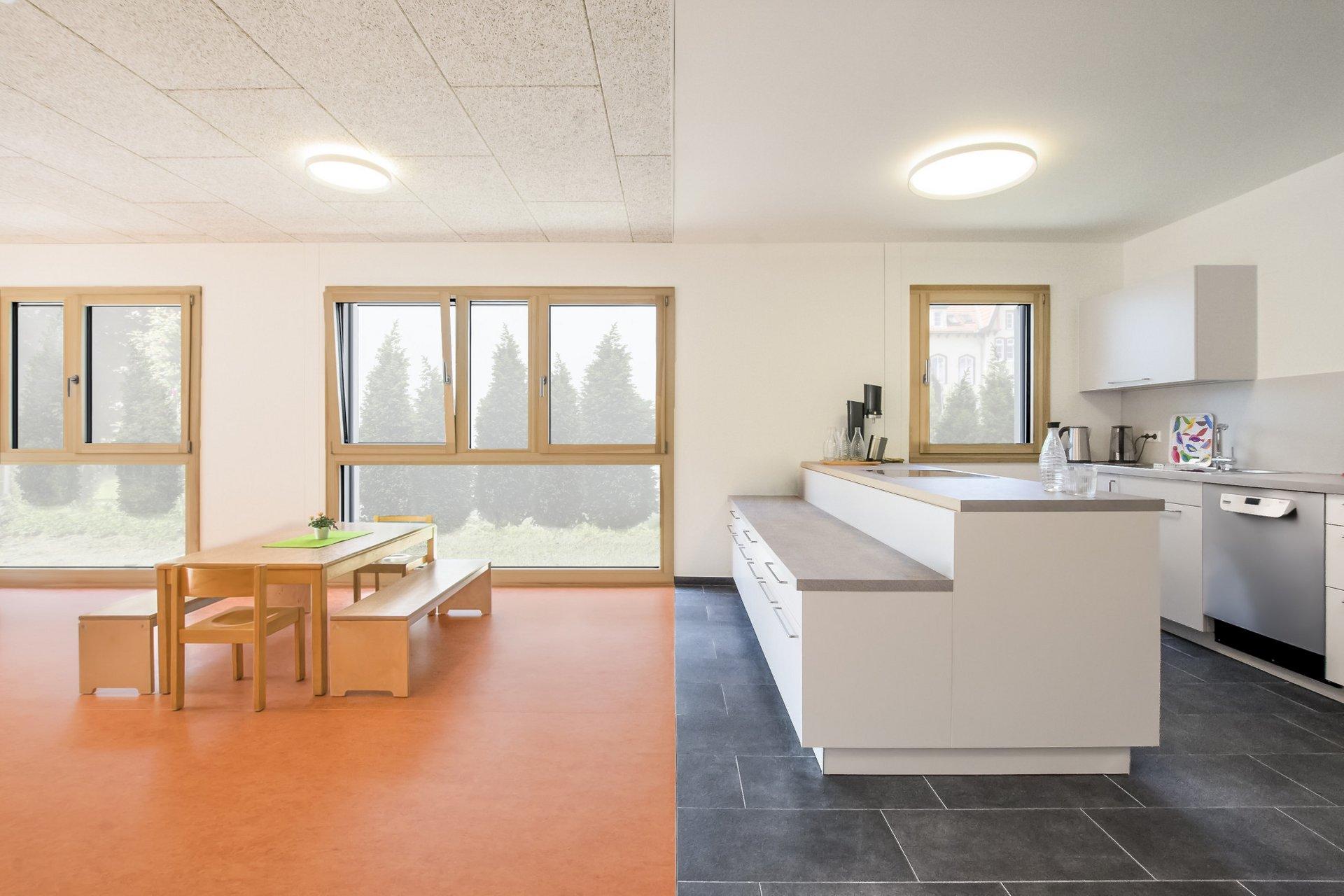 Einblick in die Küche und einen Teil des Esszimmers, mit einem Tisch welcher auf einem orangen Boden steht, während die Küche auf einem Dunkelgrauen Steinboden platziert wurde