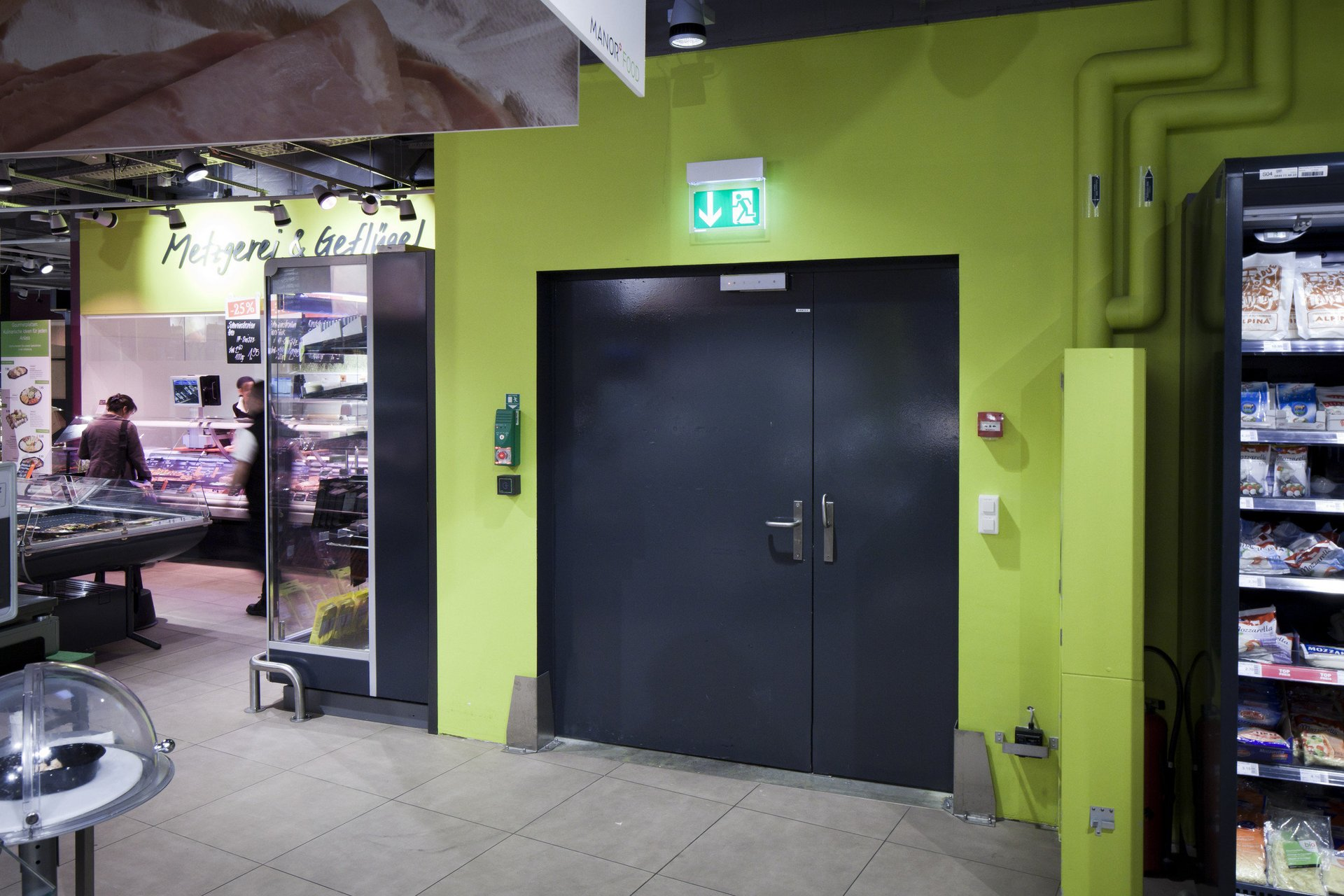 Zweiteilige Brandschutztür mit grossem und kleinem Teil und grüner Wand darum