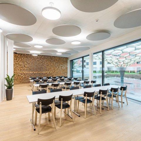 Parametrisch designte Akustikwand in Weisstanne massig in einem modernen hellen Aufenthaltsraum mit langen Tischen und Stühlen