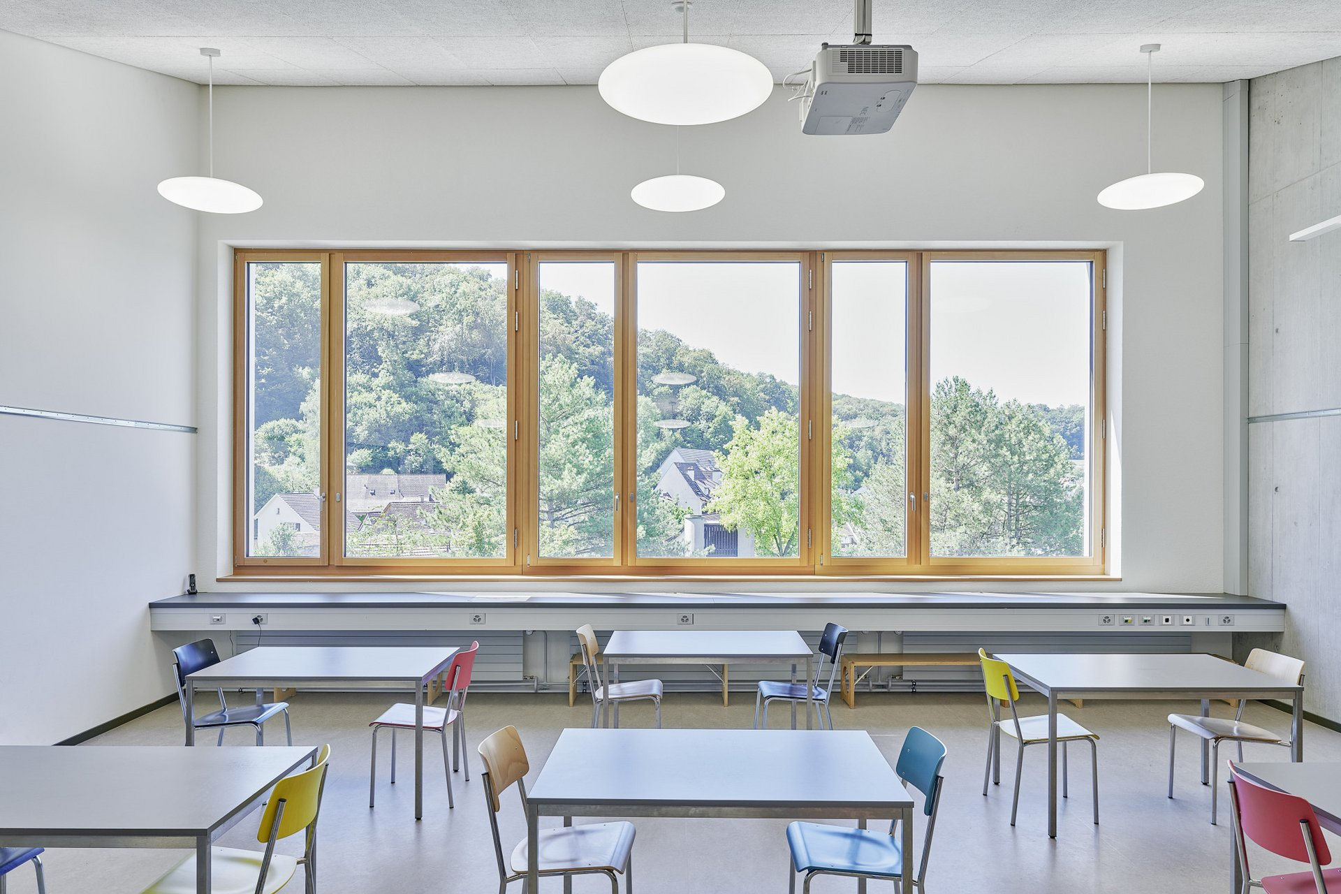 Innenraum eines modernen Schulzimmers mit grauen Tischen und farbigen Stühlen