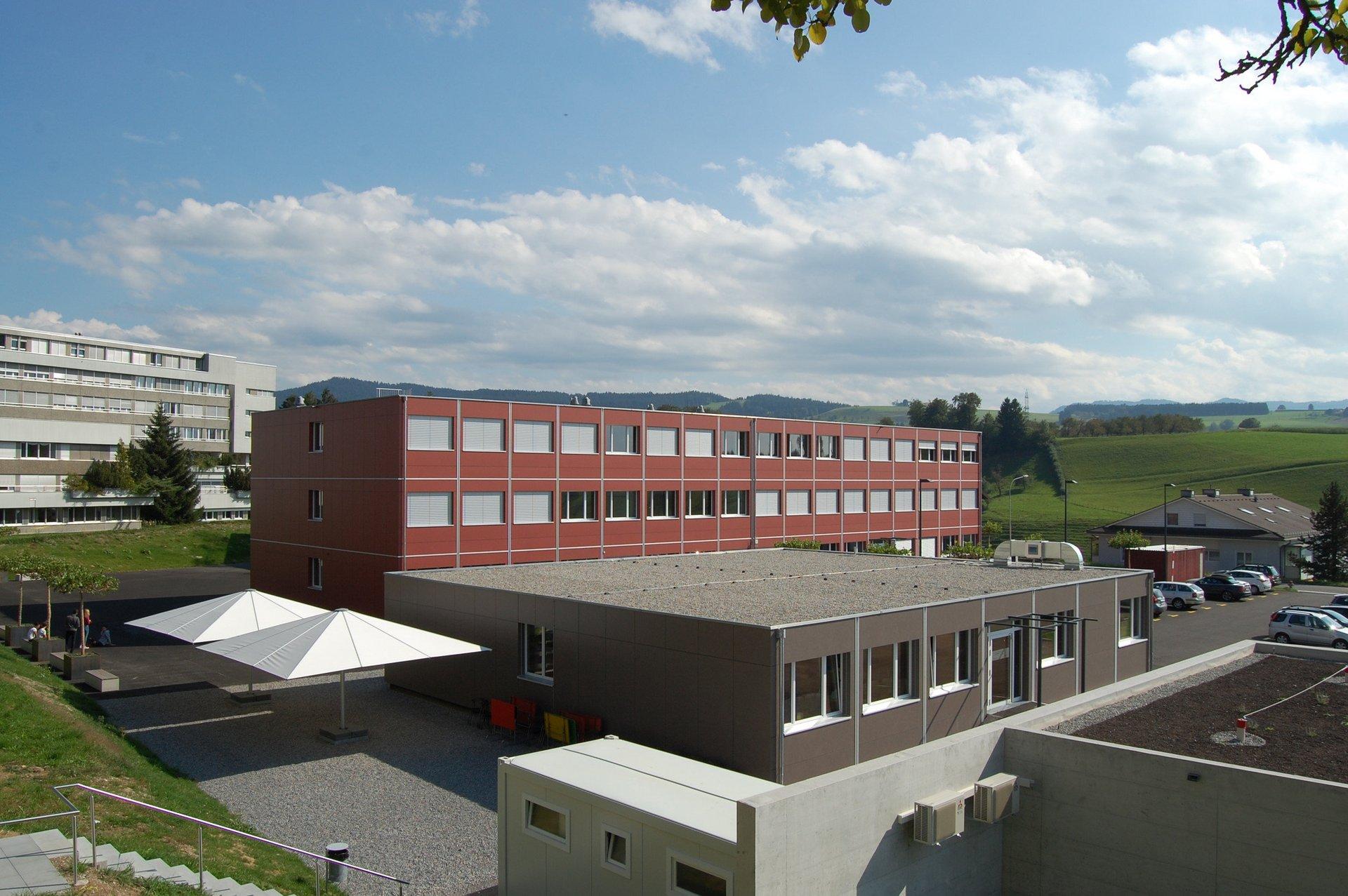 3-geschossiges Schulgebäude mit 1-geschossigem Gebäude davor