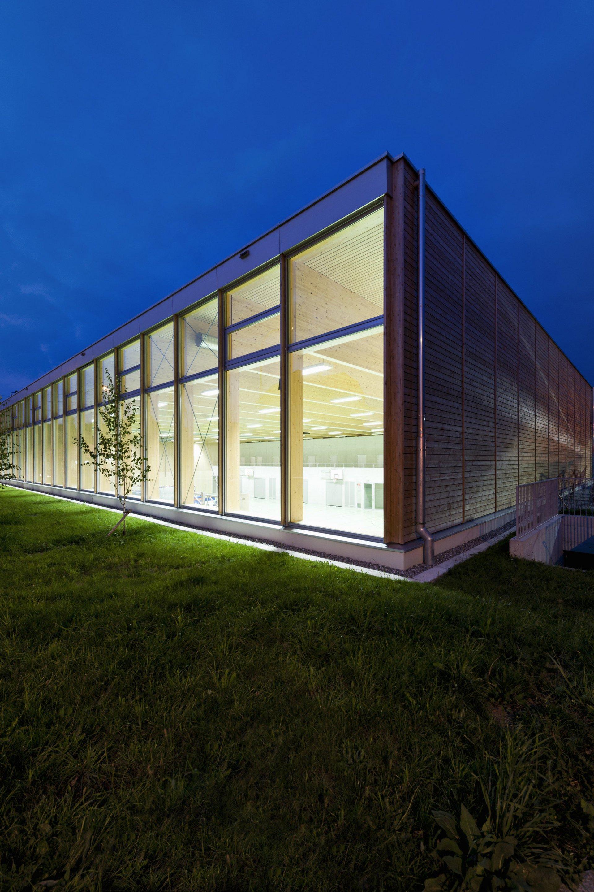 Turnhalle mit Fensterfassade bei Nacht von innen beleuchtet