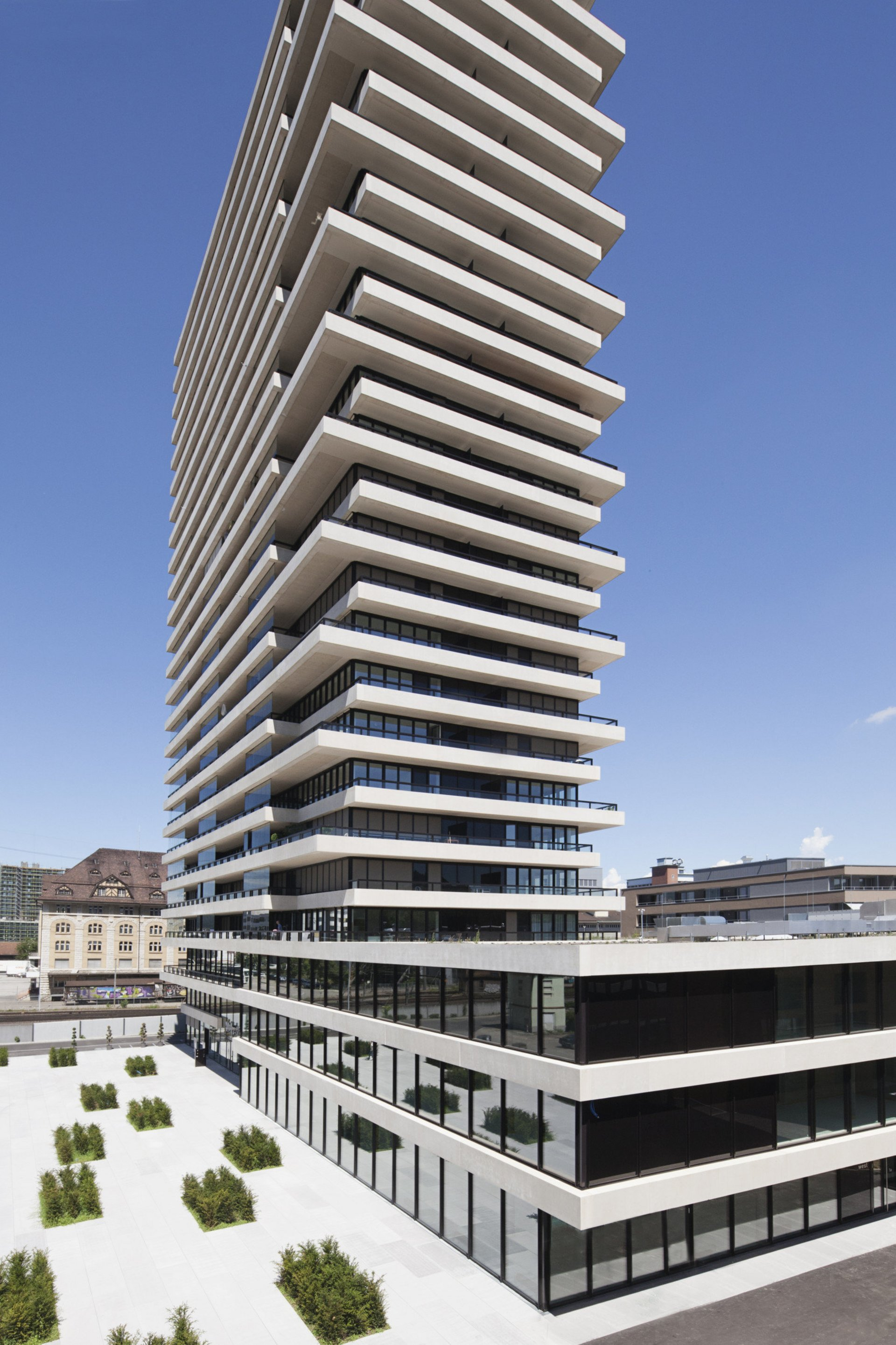 Hochhaus in spezieller Form mit Glasfront abgetrennt durch herausstehende Betonfassade