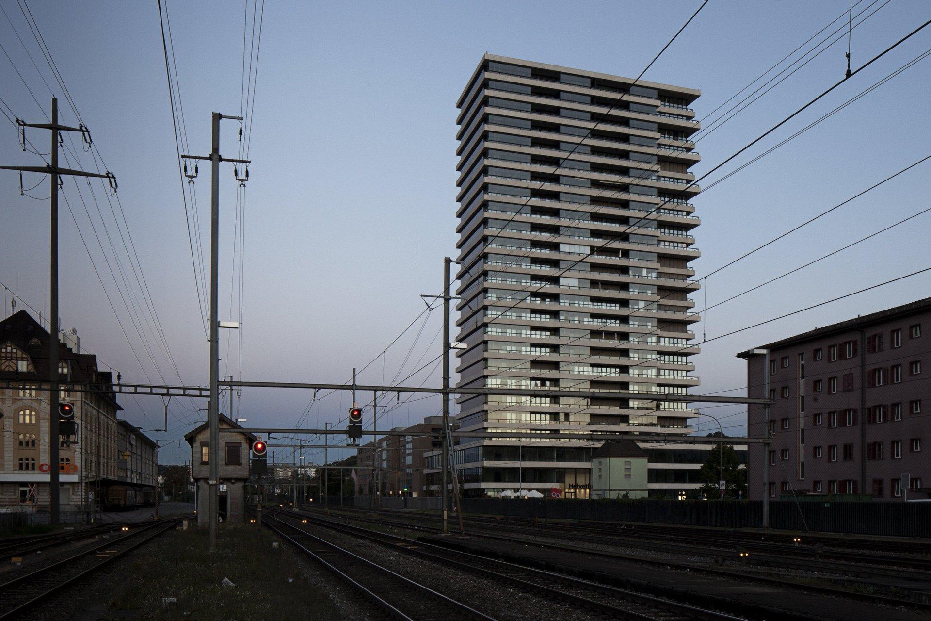 Sicht von Gleisen aus auf Hochhaus mit gleichmässiger Fensterfront und Betonfassade