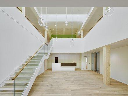 Entrée lumineuse d'un bâtiment de service avec plancher en bois et escalier vers l'étage supérieur