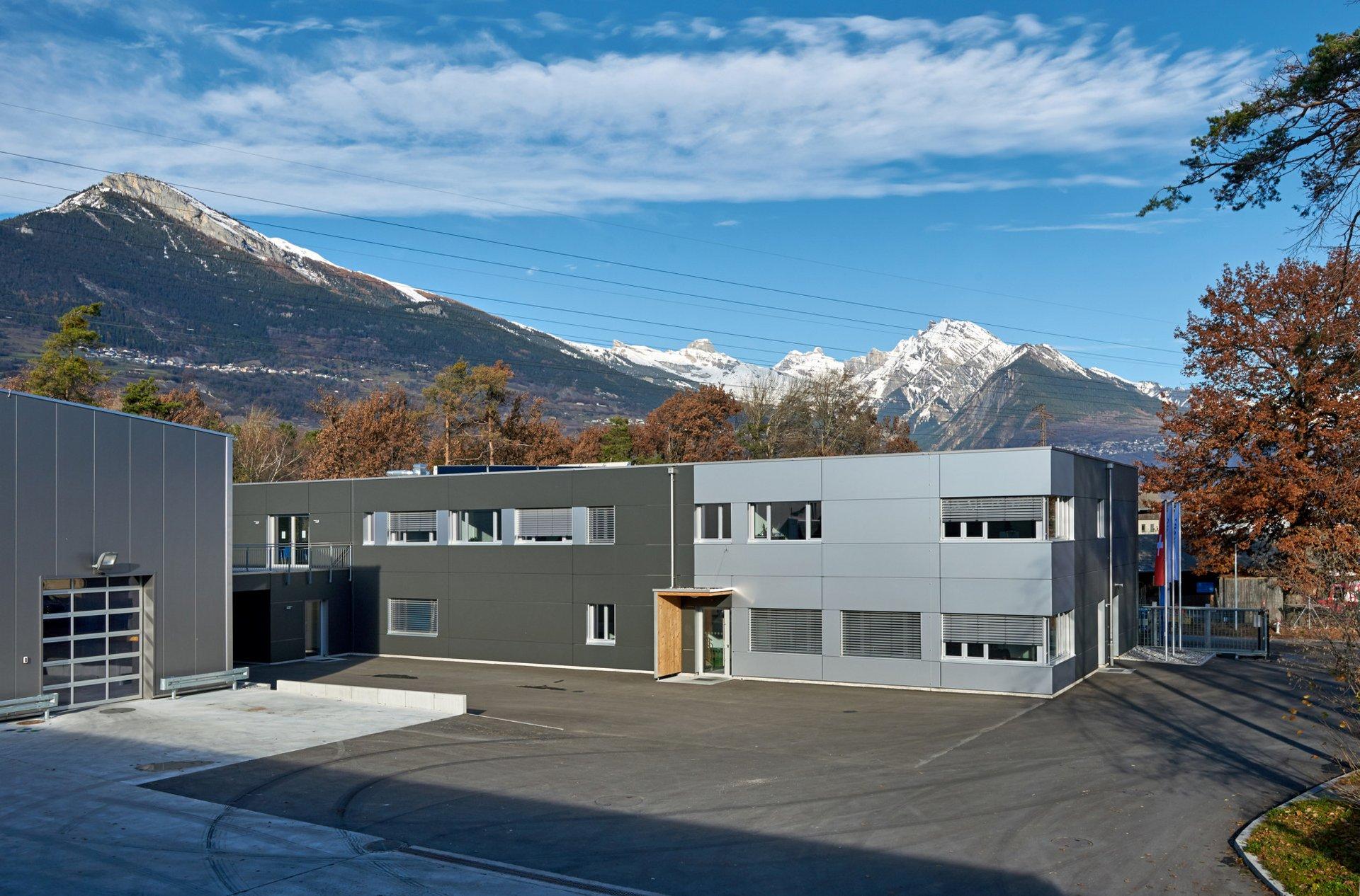 Blick auf das Verwaltungsgebäude und den dahinterliegendem Bergpanorama