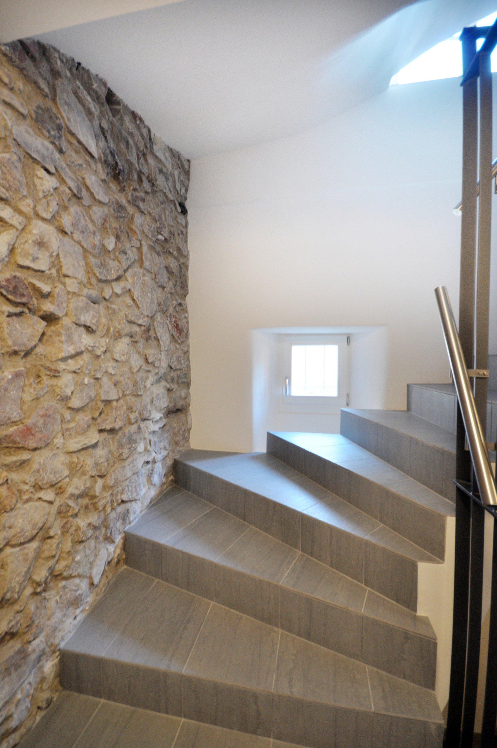 Treppe mit kleiner Fensternische und Steinwand in altem stilistischen Design