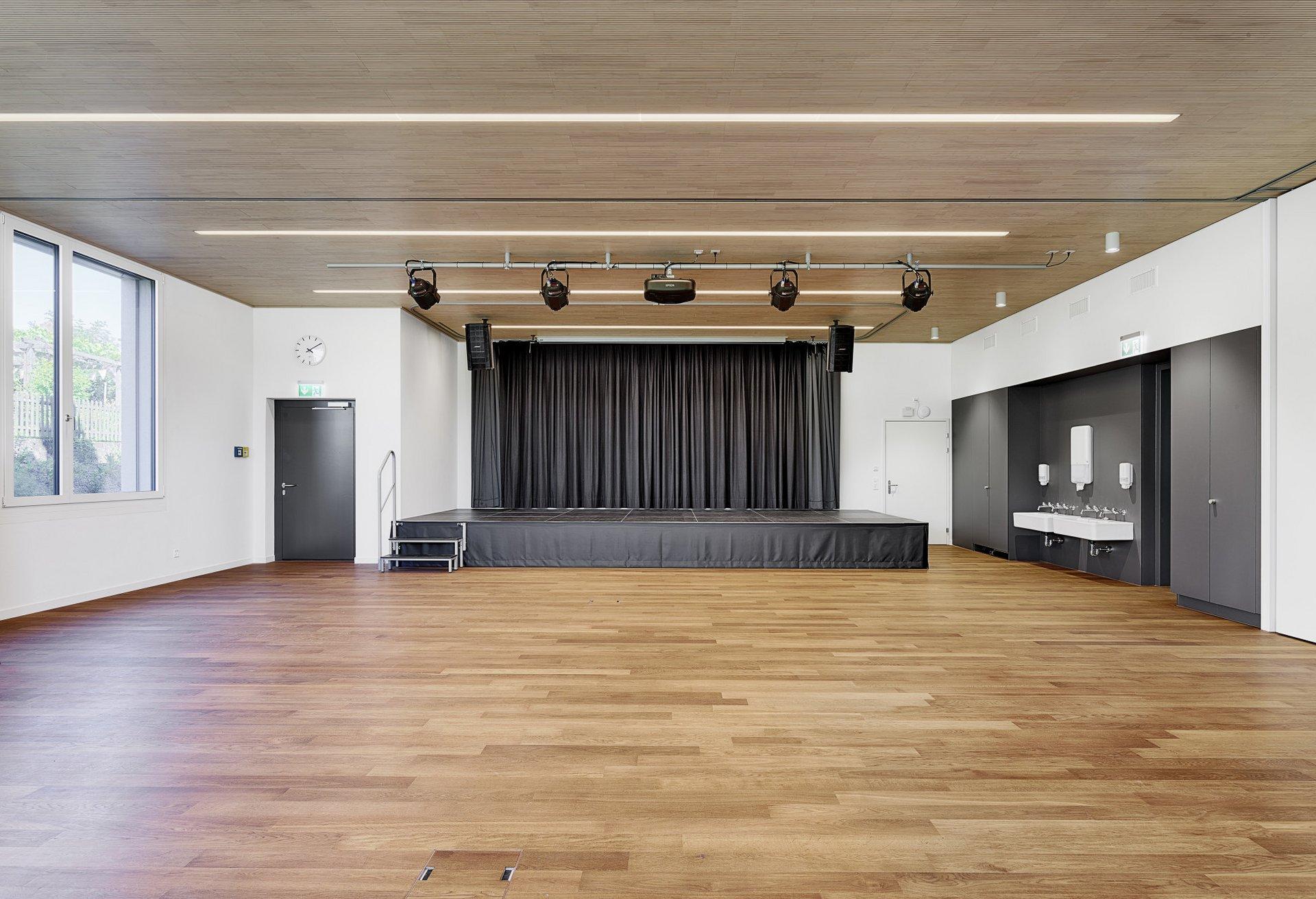 Blick in die Aula und der darinstehenden Bühne und den allesamt in dunkelgrau gehaltenen Hölzernen Wandschränken
