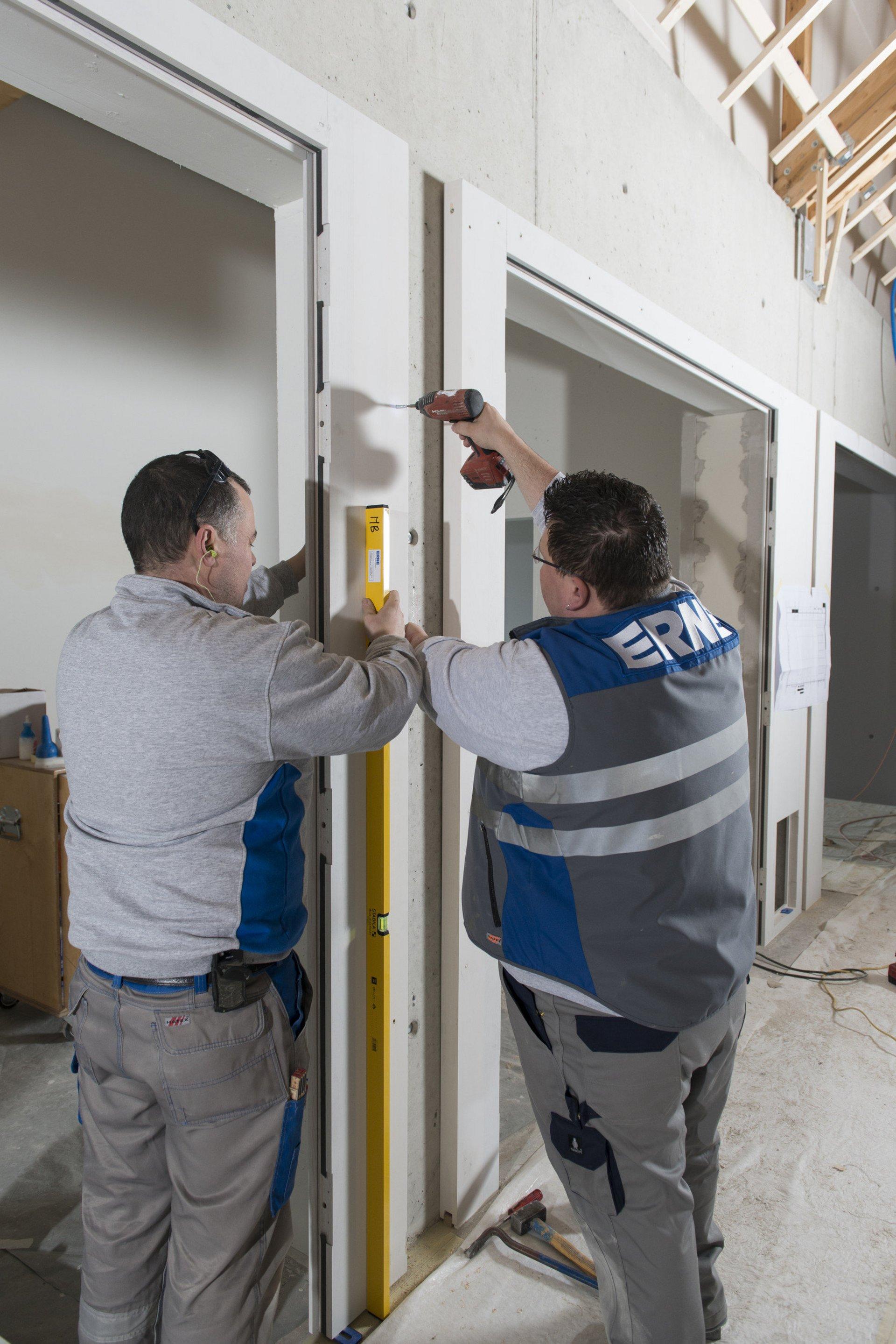 2 ERNE Mitarbeiter während der Montage einer Brandschutztür