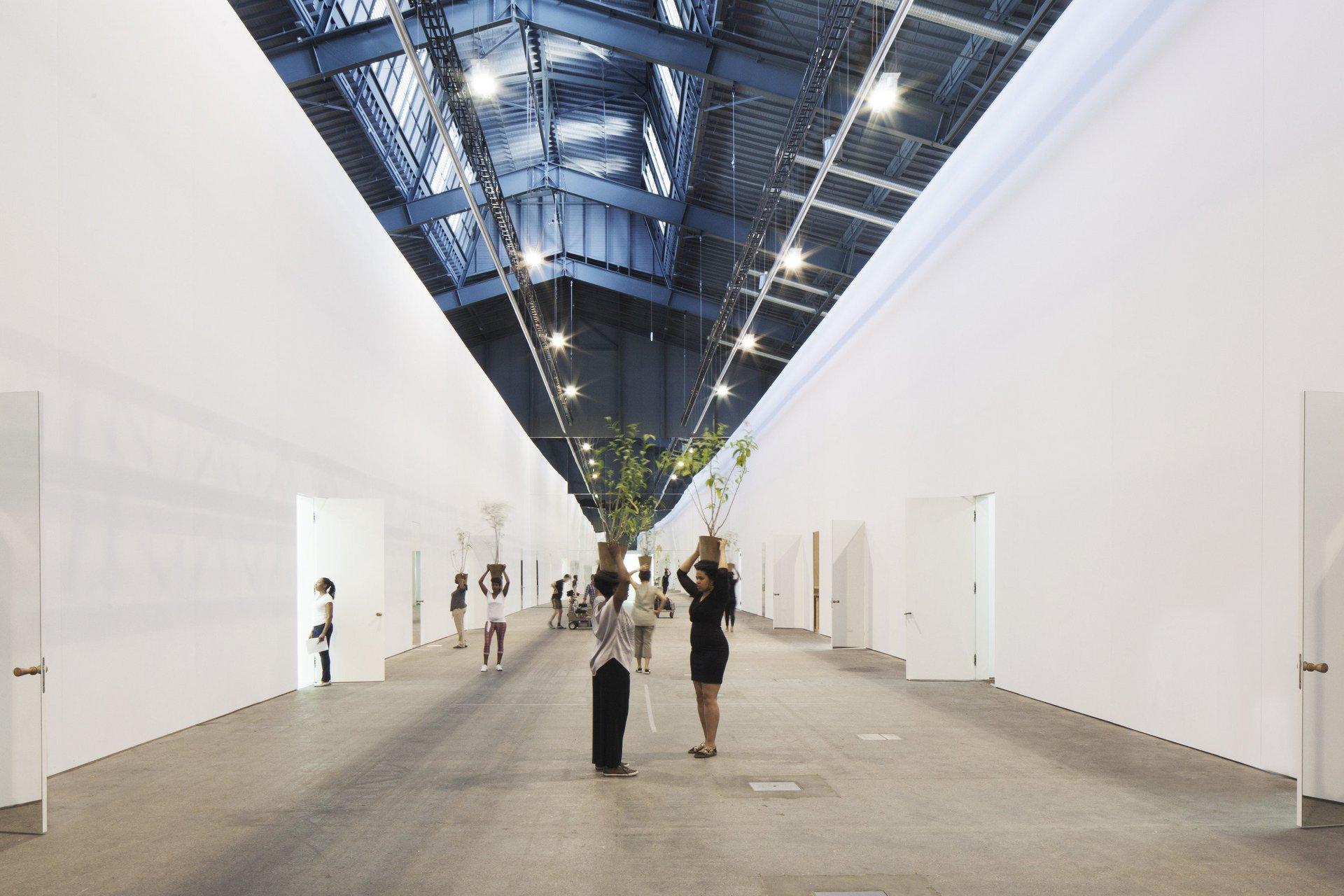 Halle mit hohen weissen Wänden und Menschen mit Blumentopf auf Kopf