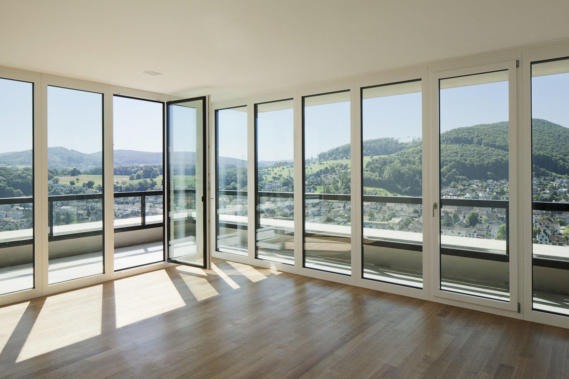 unmöblierter Raum mit Fensterfront aus Holz-Metall in hellem und modernem Design