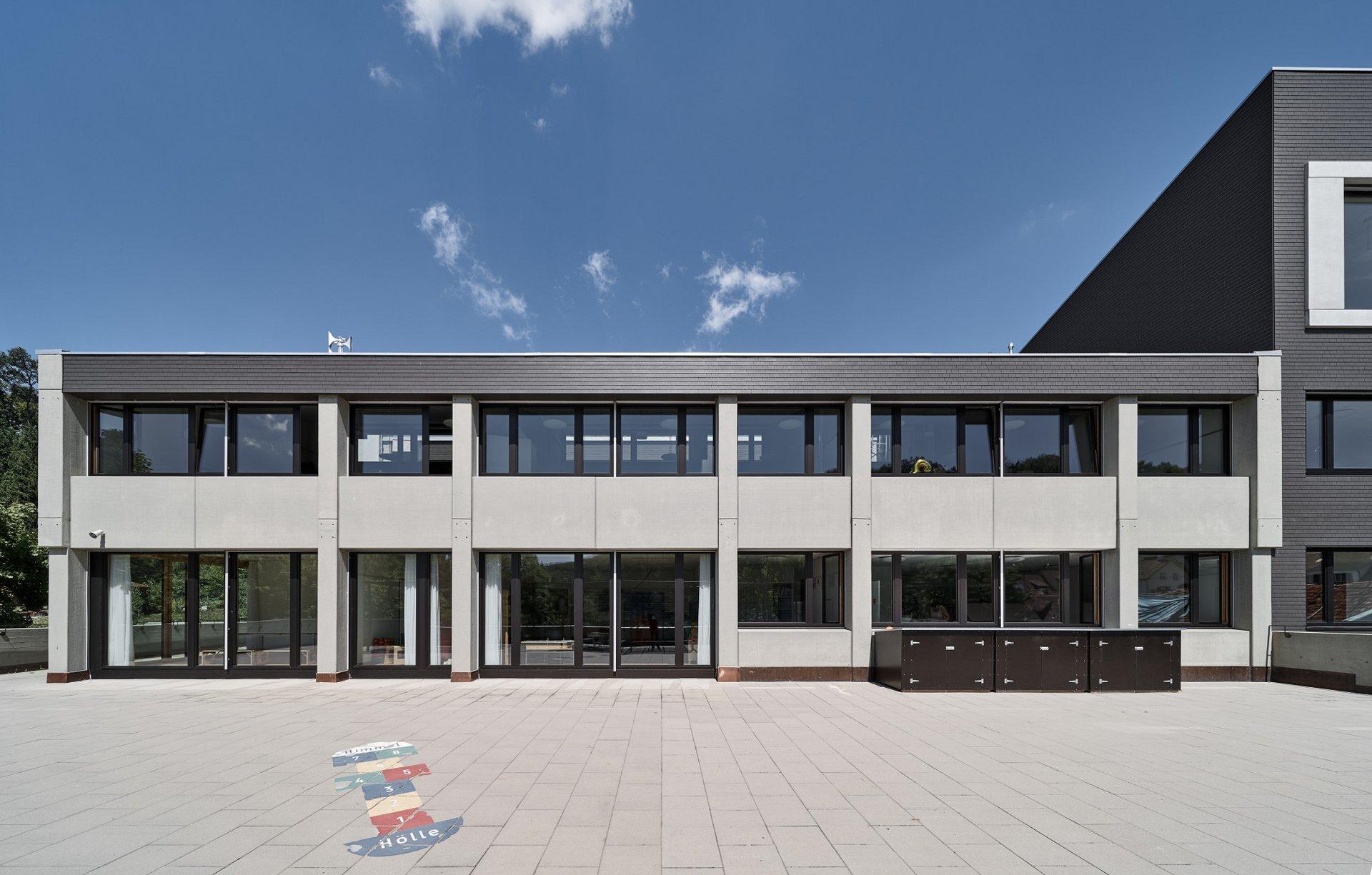 Blick auf ein zweistöckiges Schulgebäude mit Beton Elementen und schwarzem Holzdach