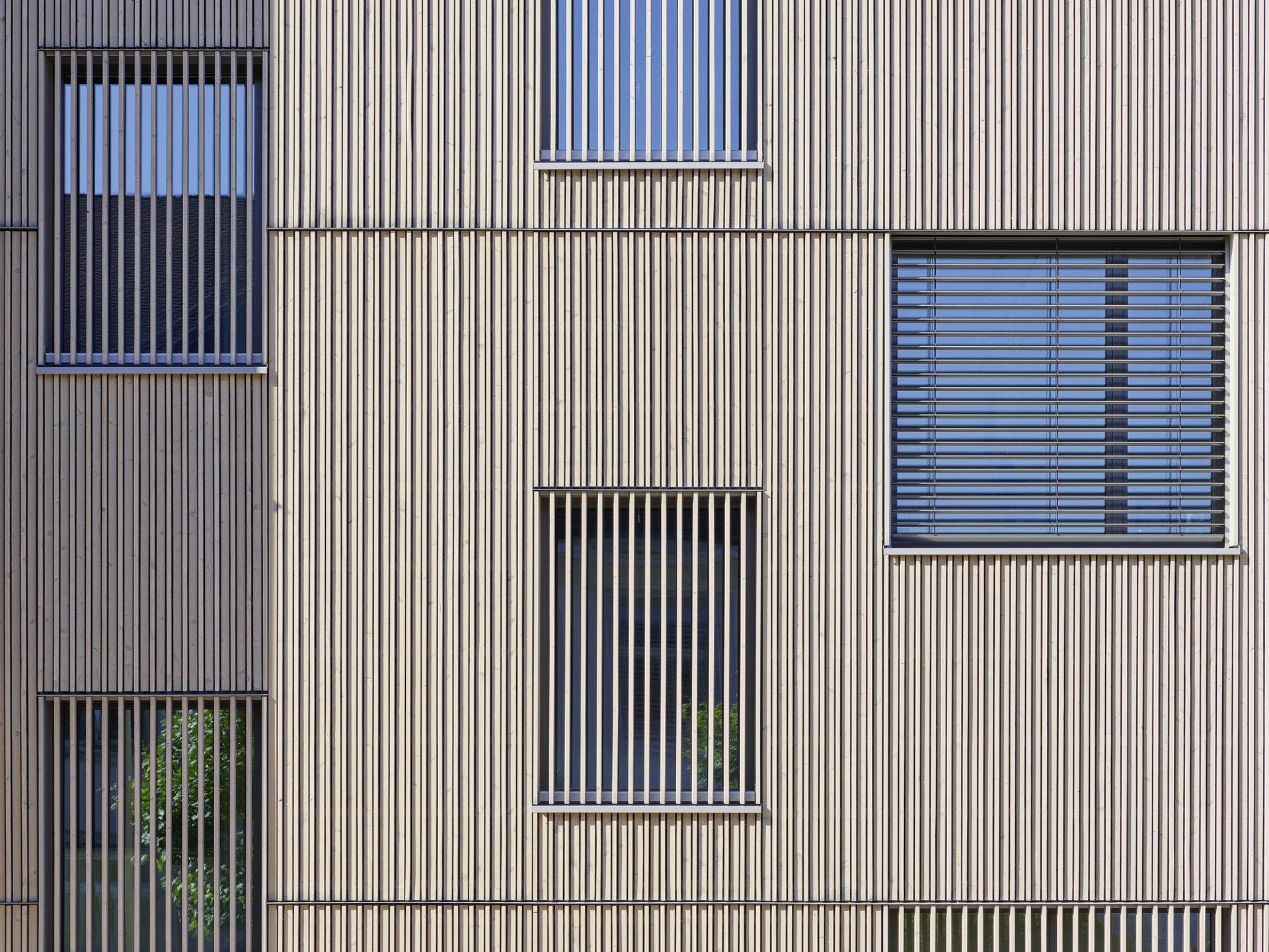 Fassadenausschnitt mit Fenstern welche mit Holz eingegittert sind oder durch die Storen abgedunkelt wurden.