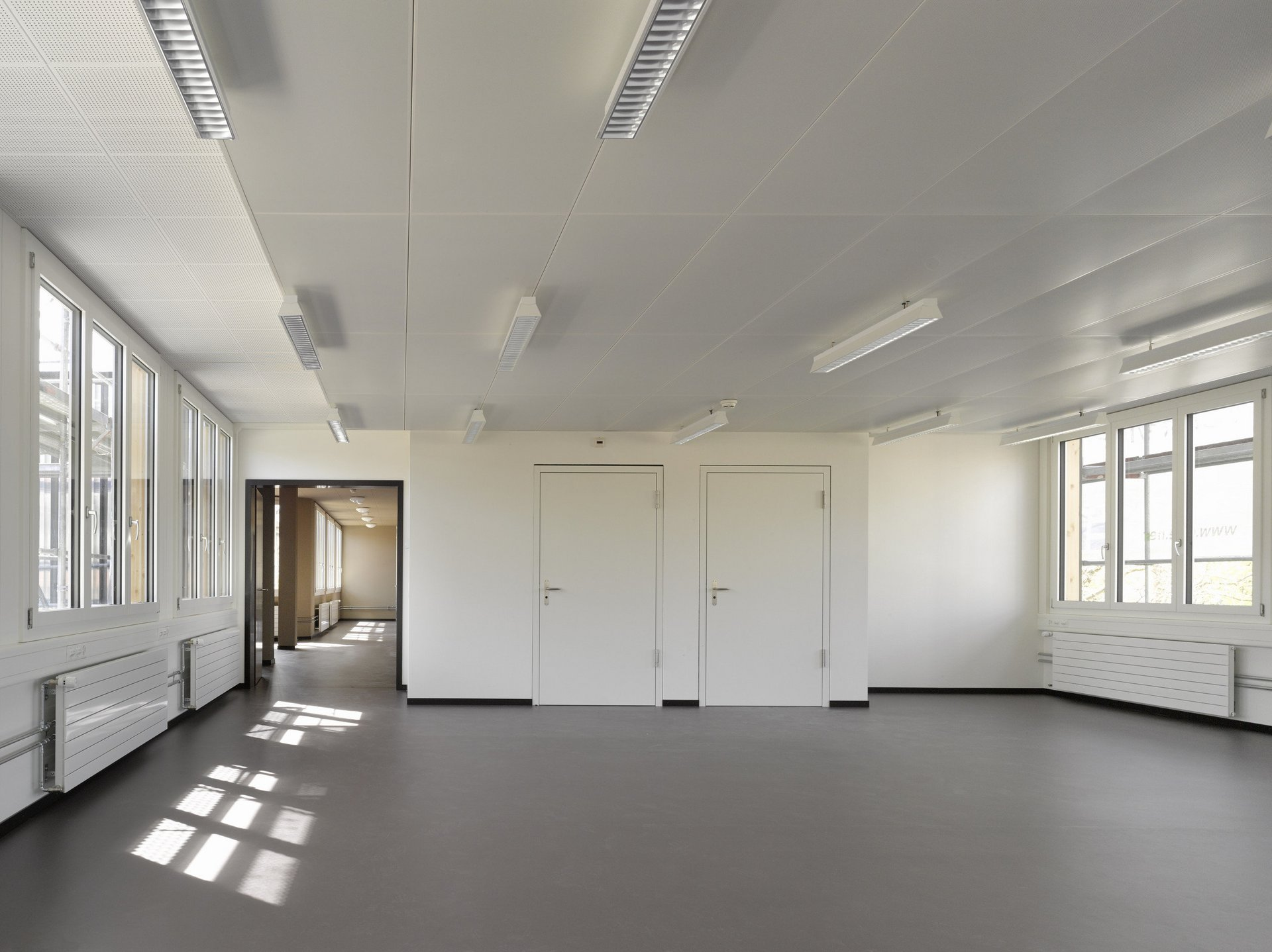 lichtdurchfluteter Raum mit grossen Fensterelementen auf beiden Seiten