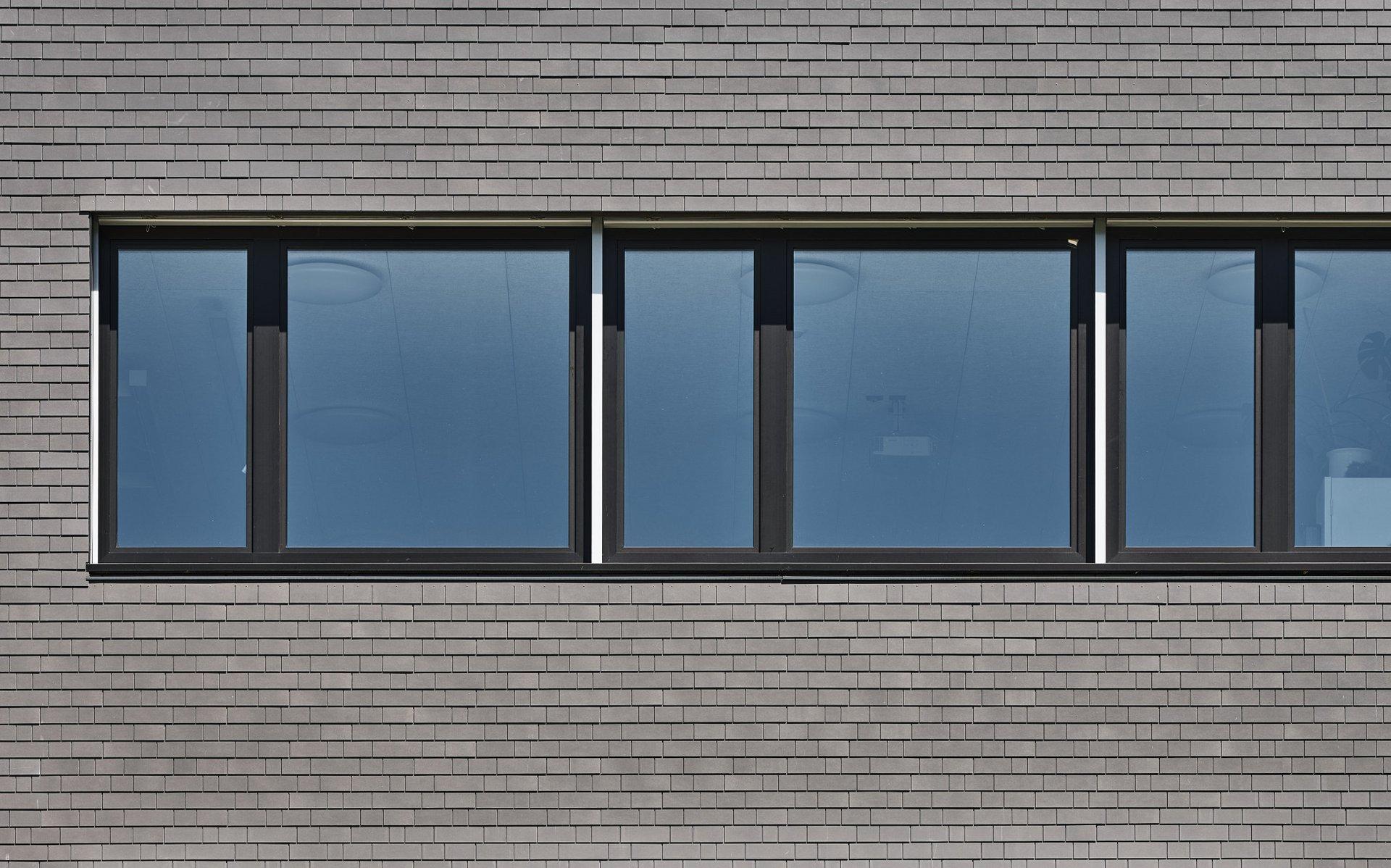 Blick auf einen Fassadenausschnitt mit blau schimmernden Fenstern welche über schwarze Rahmen verfügen