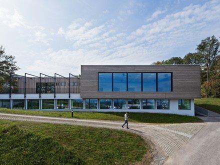 Modernes Schulgebäude mit grosser Fensterfront und einer Fassade aus Holz
