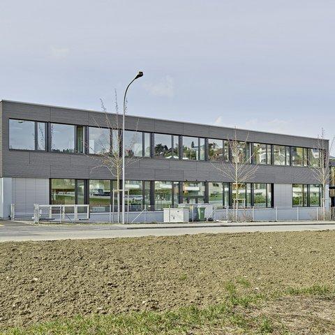 Zweigeschossiges Schulgebäude mit grauer Holzfassade und grosszügigen Fenster.
