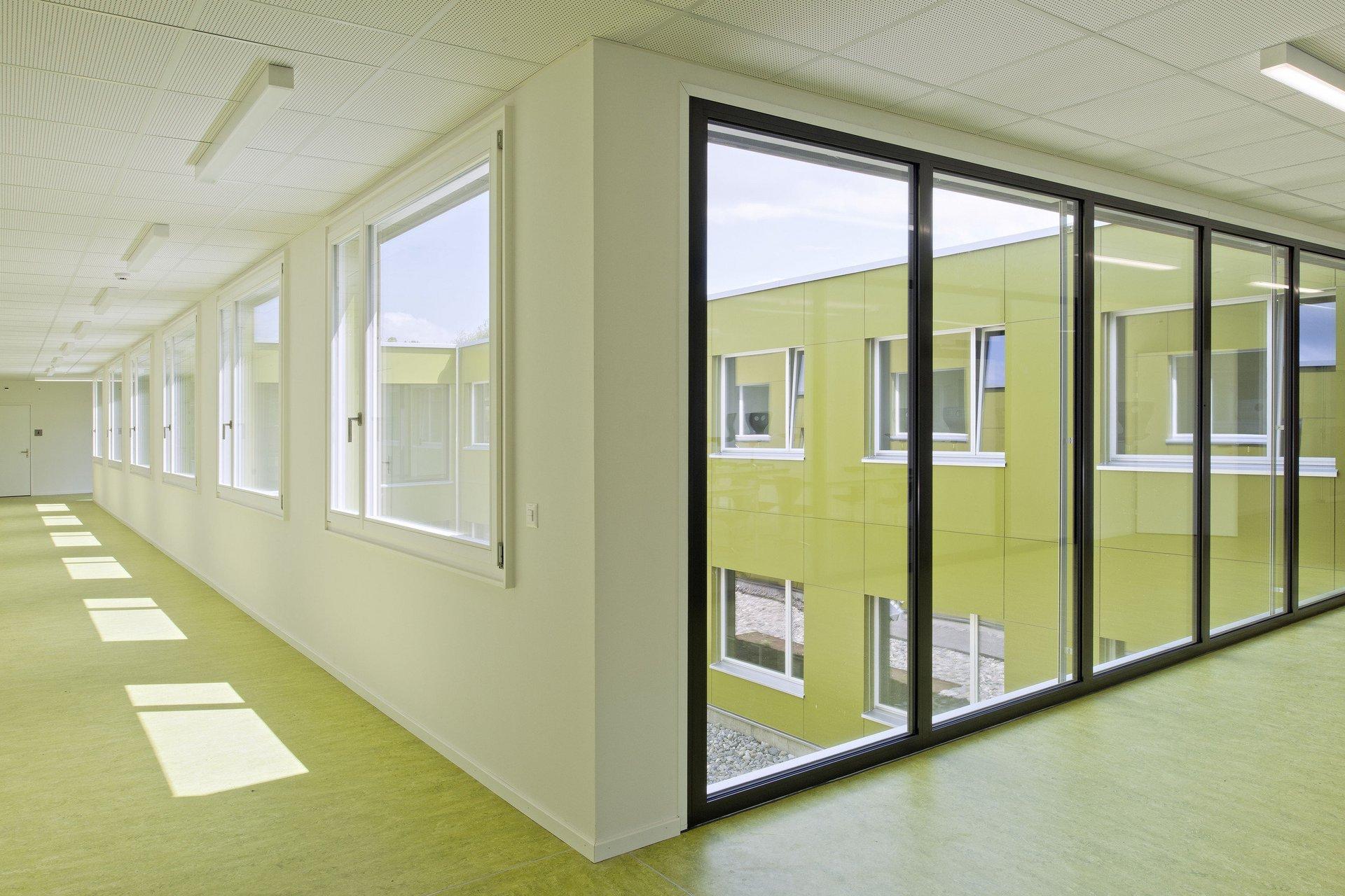 Lichtdurchfluteter Flur in Schulgebäude mit Glaswand und gleichmässig grossen Fenstern