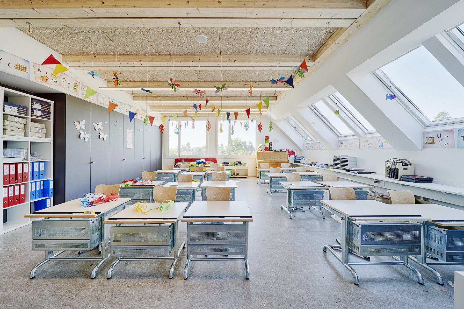 Blick in ein Klassenzimmer mit dunkelgrauen Wandschränkem, einer hölzernen Decke und viele Stühle mit Tischen