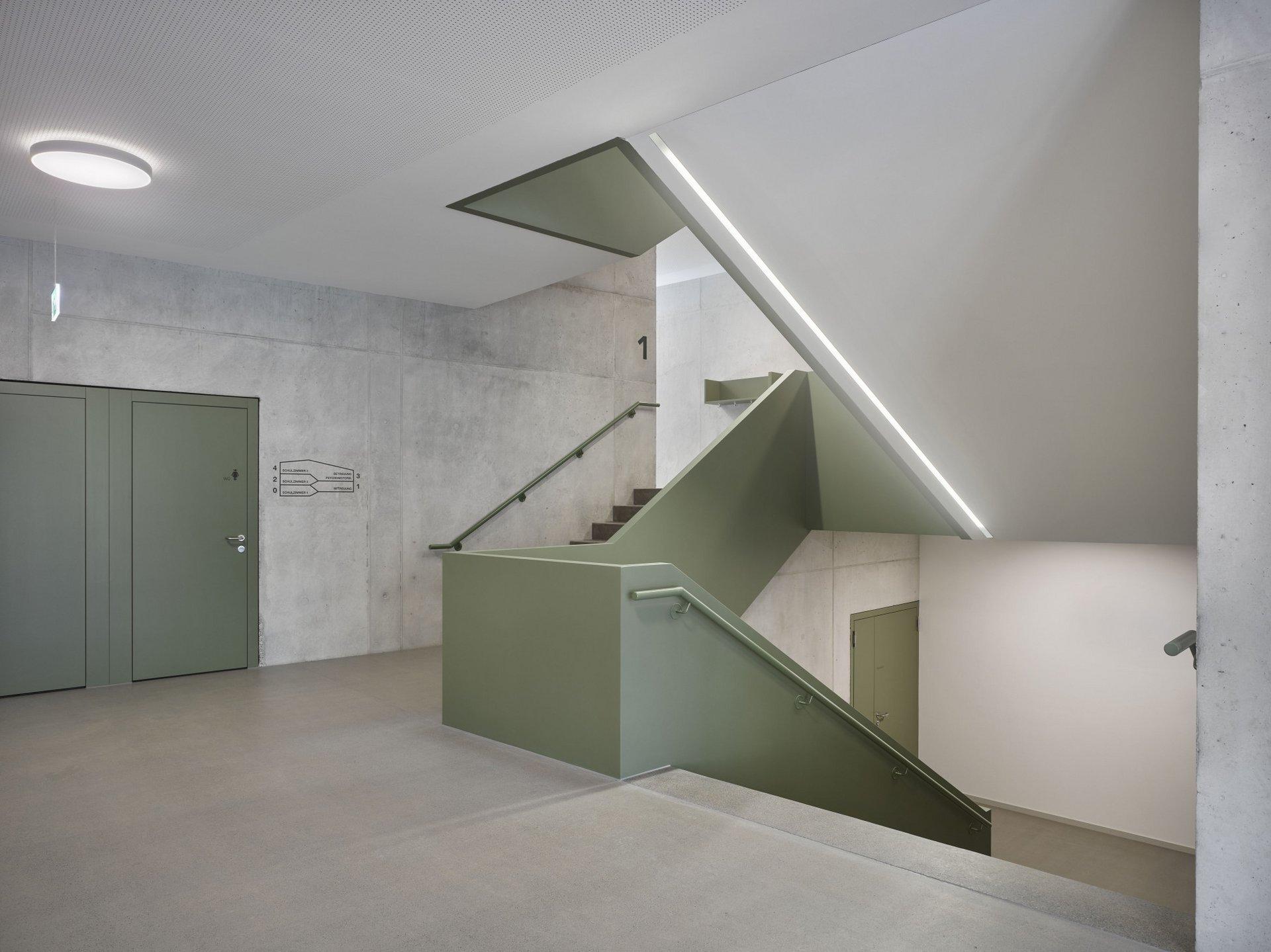Treppenhaus mit Betonwänden und olivgrünen Geländern und Türen.