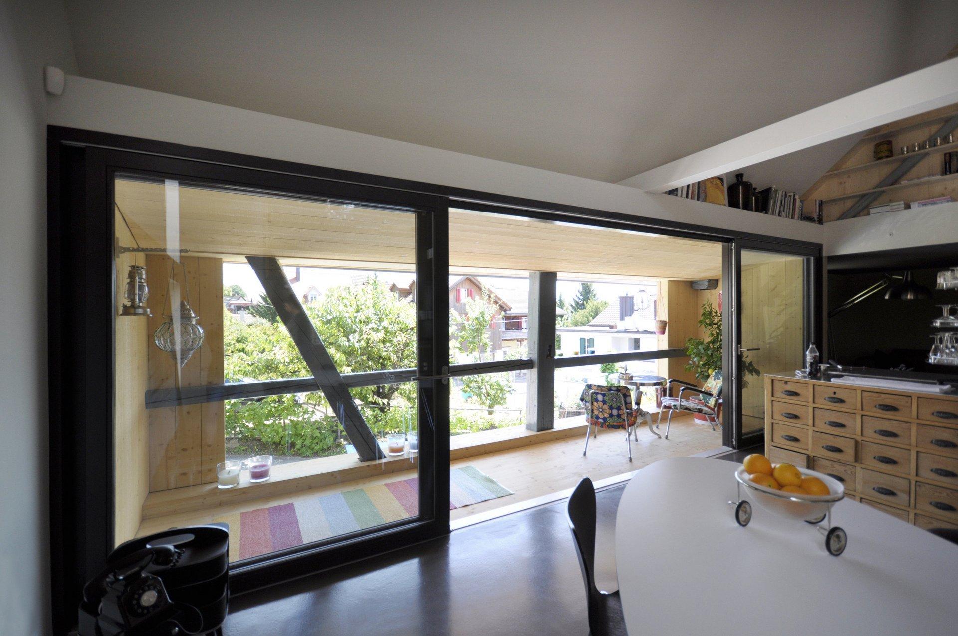 Möblierter Wohnbereich mit Fokus auf grosse Hebe-Schiebetüren die die Wand ersetzen