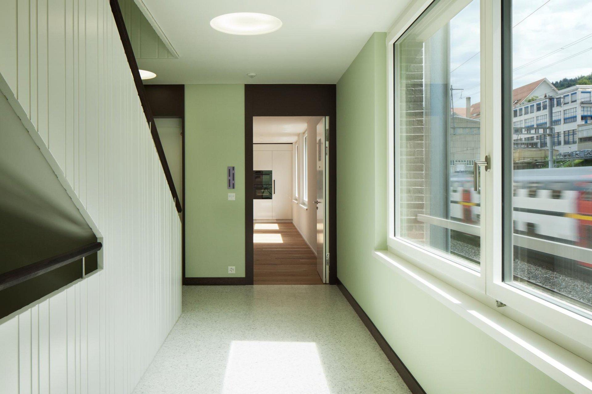 Treppenhaus in grün mit Holz-Metallfenstern mit Schallschutzanforderungen
