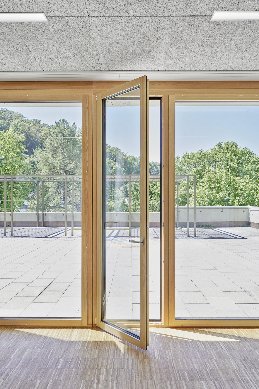 Eine offenstehende Balkontür aus Holz, welche auf die sonnenbestrahlte Terrasse führt.