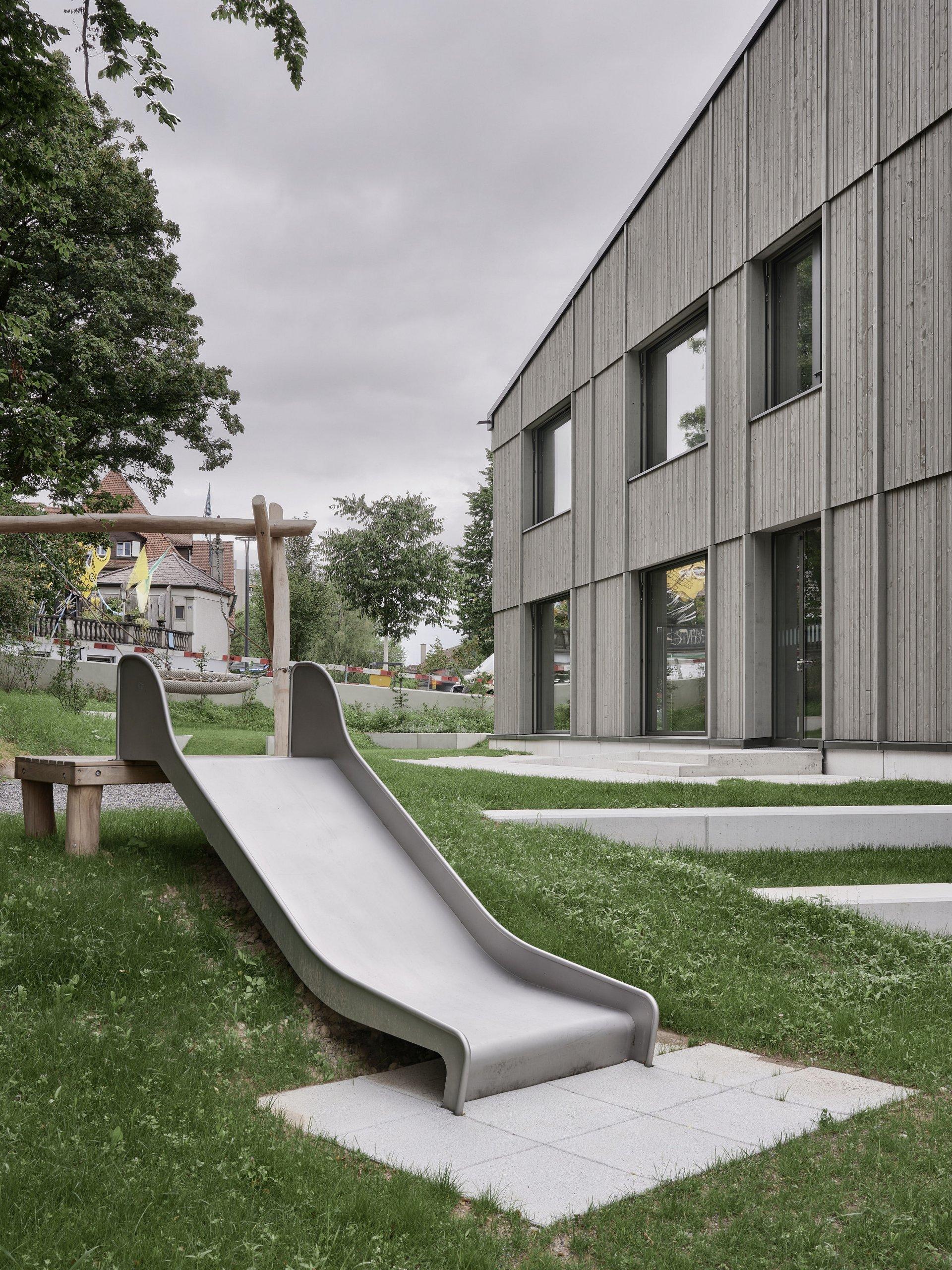 Eine breitgebaute metallene Rutschbahn auf dem Vorplatz eines Schulhauses.