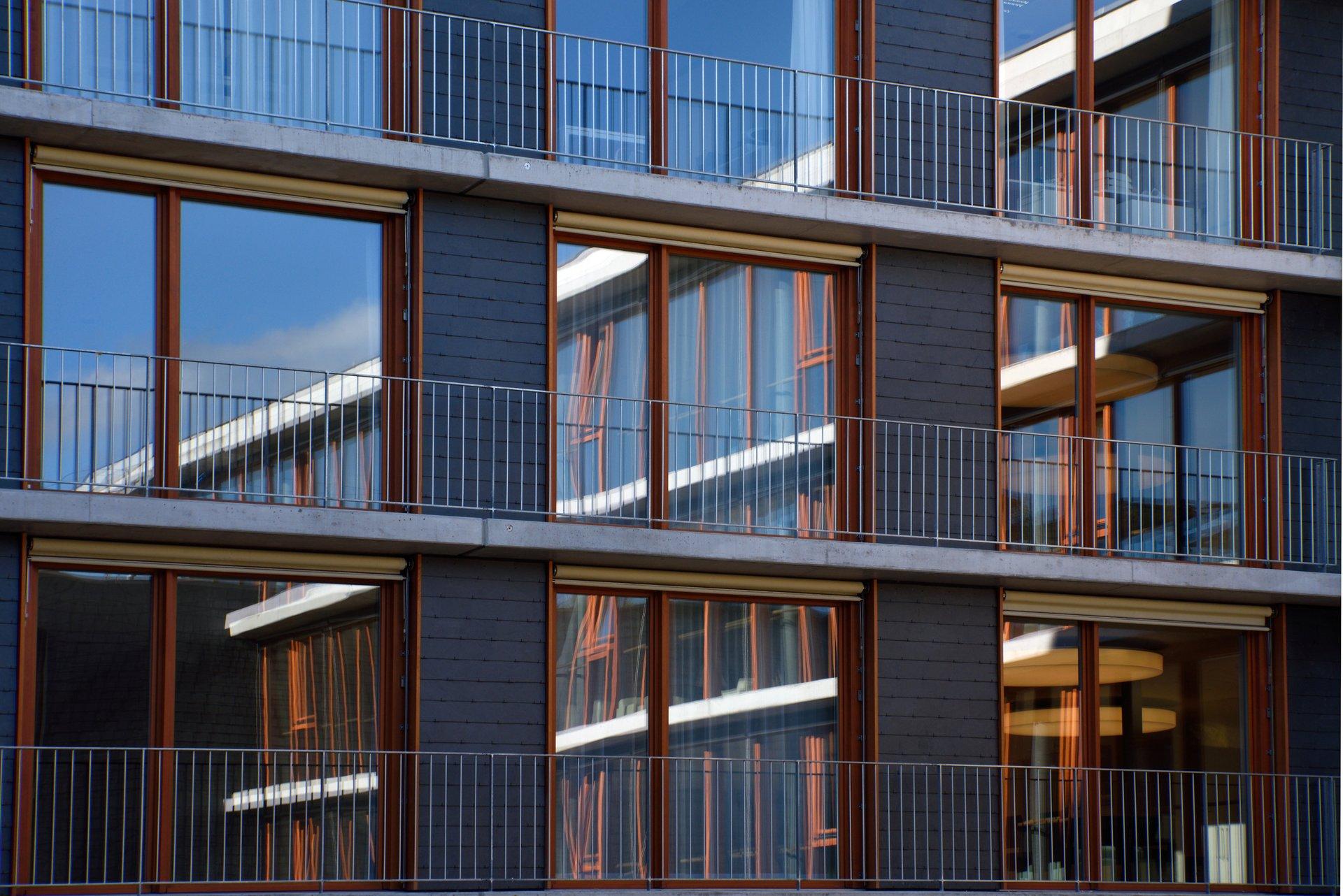 Fensterfront aus Holzfenster bei mehrstöckigem Gebäude mit speziellen Leibungsaufdoppelungen