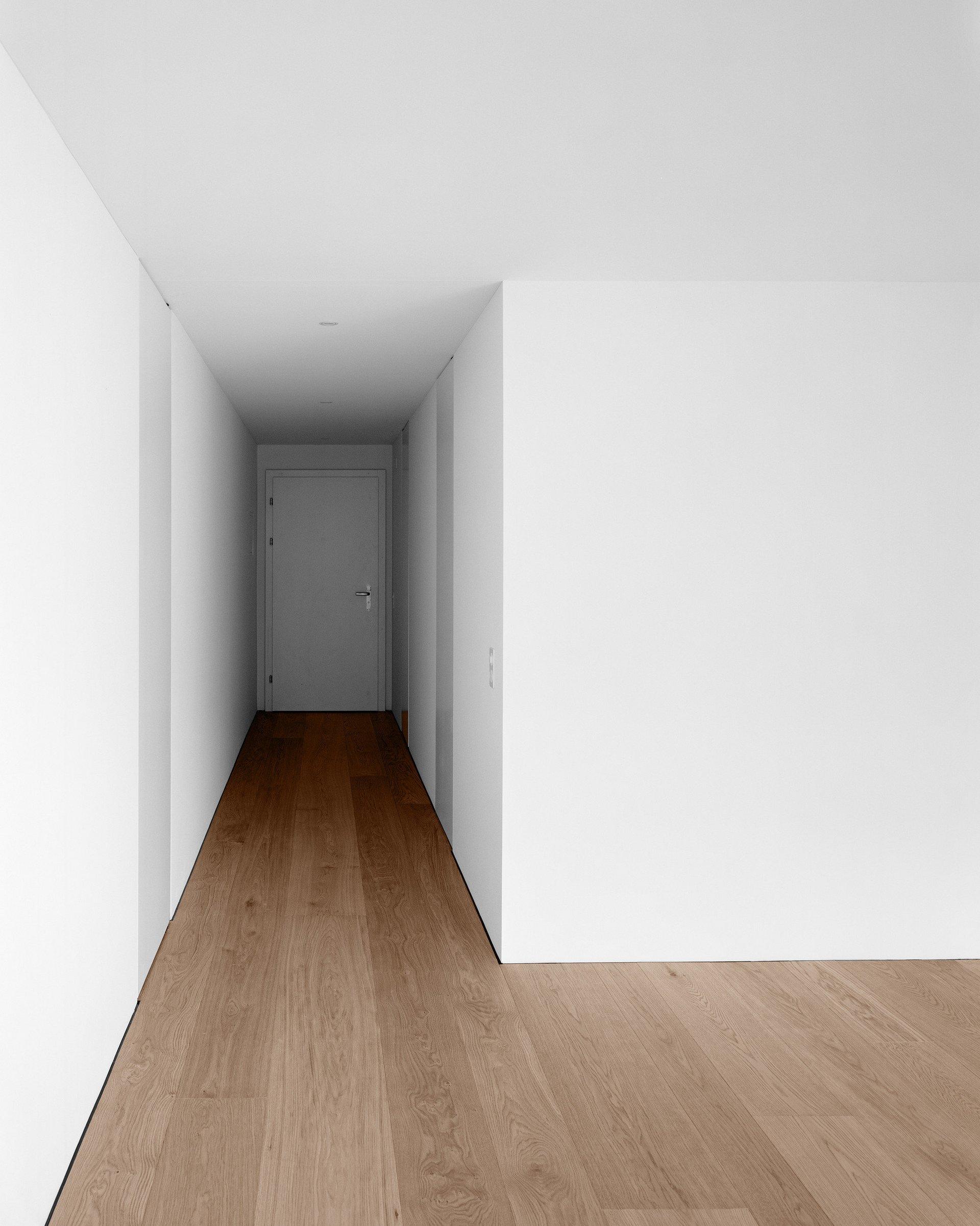 sanierter Flur mit weissen Wänden und Türen und dunklem Holzboden