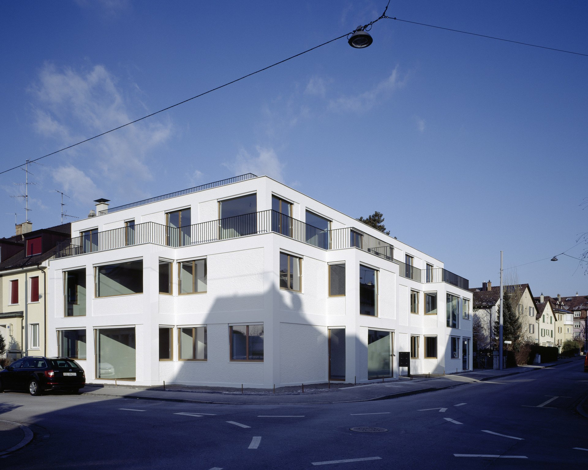 2-stöckiges Wohngebäude mit verschieden grossen Fenstern und weisser Fassade