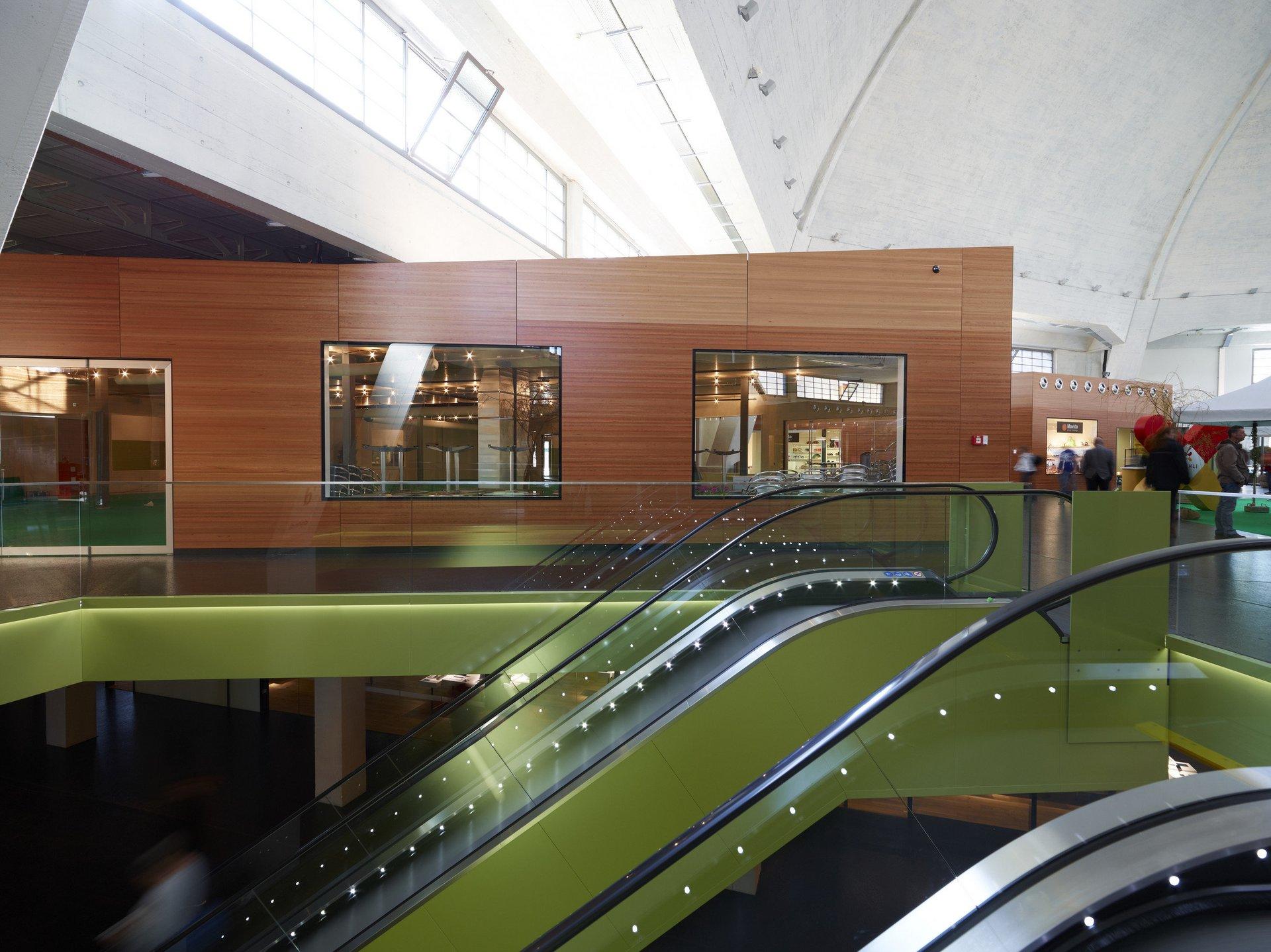 Sicht auf Shop-in-Shop in Holz mit 2 grün verkleideten Rolltreppen davor