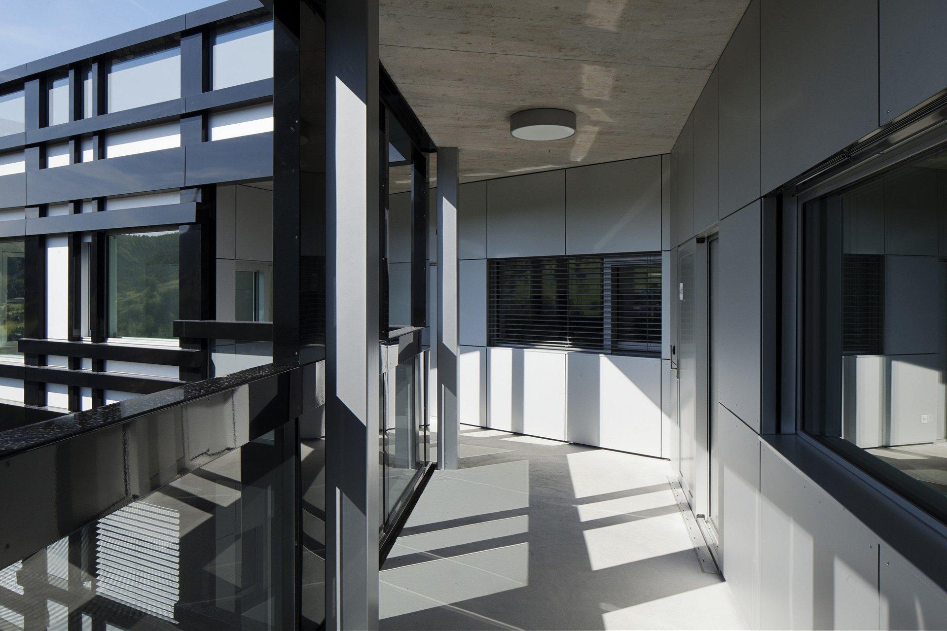 überdachter Terrassenteil mit Abzweigung nach links auf mehrgeschossigem Gebäude