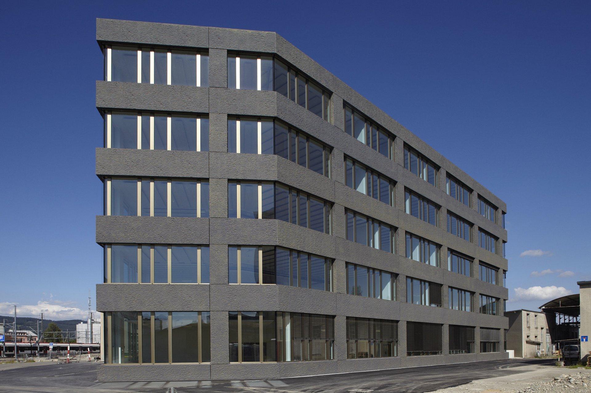 Mehreckiges Bürogebäude mit grossflächigen Lichtbänder in Holz-Metall