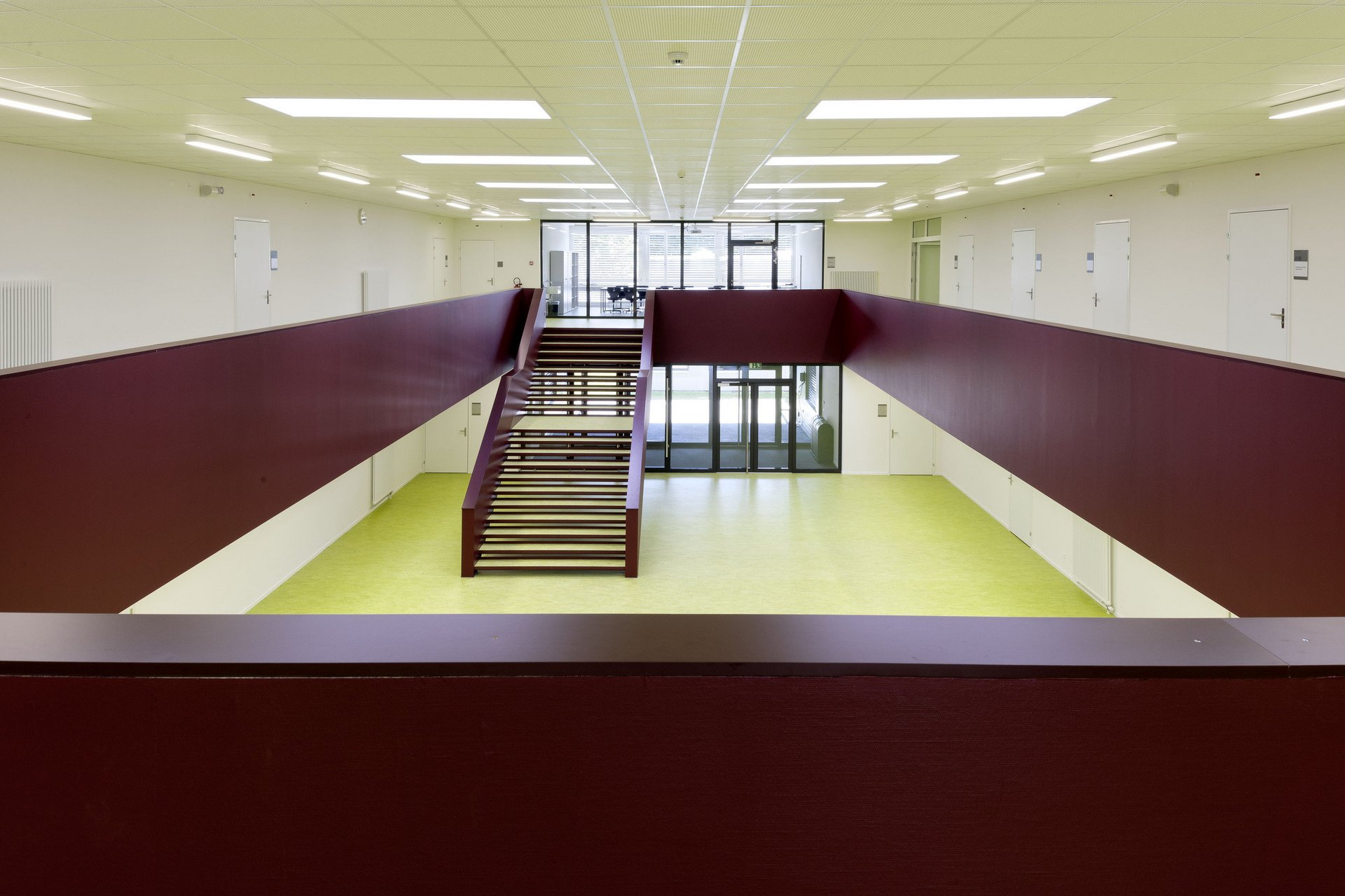 Schulgebäude von innen mit Sicht von 1. OG auf Innenhof im EG und auf rote Holztreppe