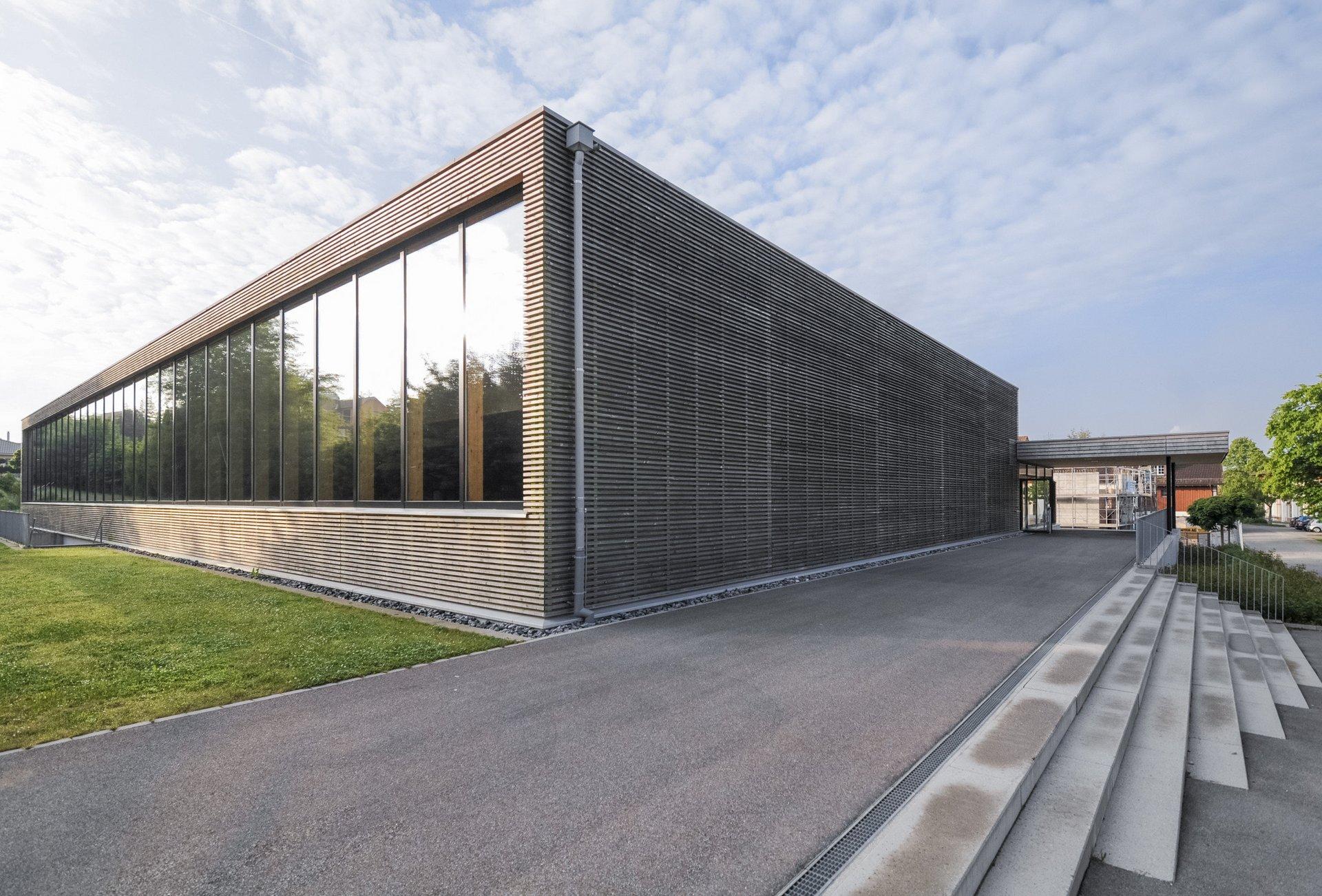 Sporthalle mit Fassade aus Holzlamellen quer