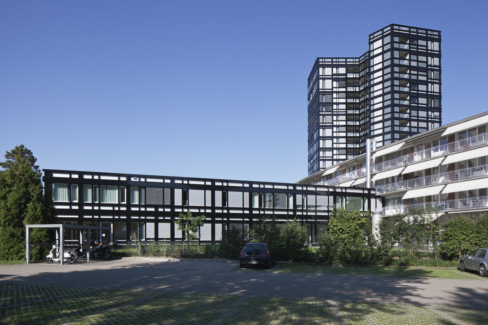 2-geschossiges Gebäude mit Hochhaus rechts hintendran mit schwarzer Fassade