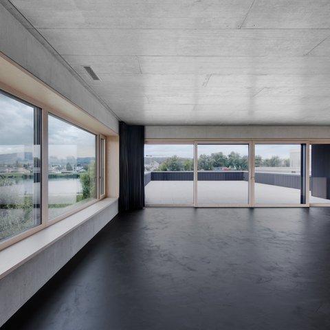 Grosses Wohnzimmer ohne Einrichtung mit grossen Holz-Metallfenster und Hebe-Schiebetüren in Esche