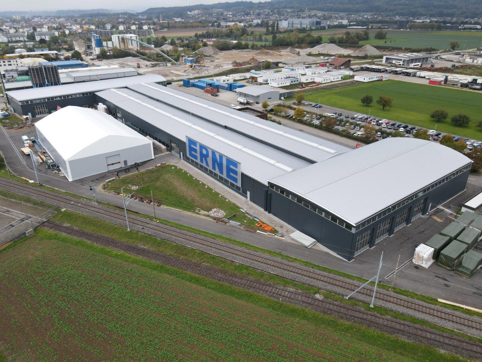 Luftaufnahme der Produktionshalle, eingehüllt in einer Anthrazitfarbenen Fassade mit einem Dach aus Metall.