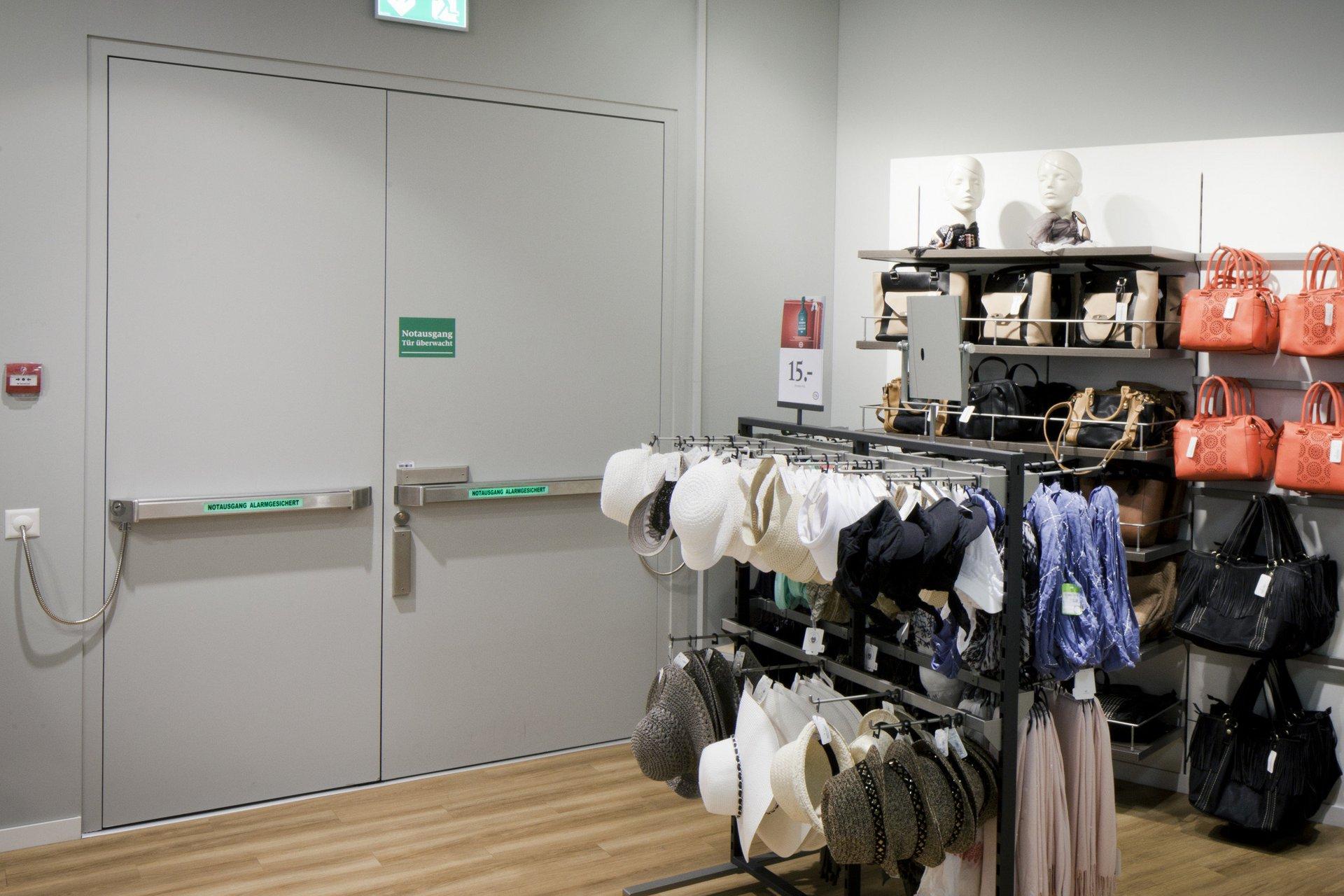 Zweiflügelige Brandschutztür in grau in einem Shop neben Taschen und Hüte