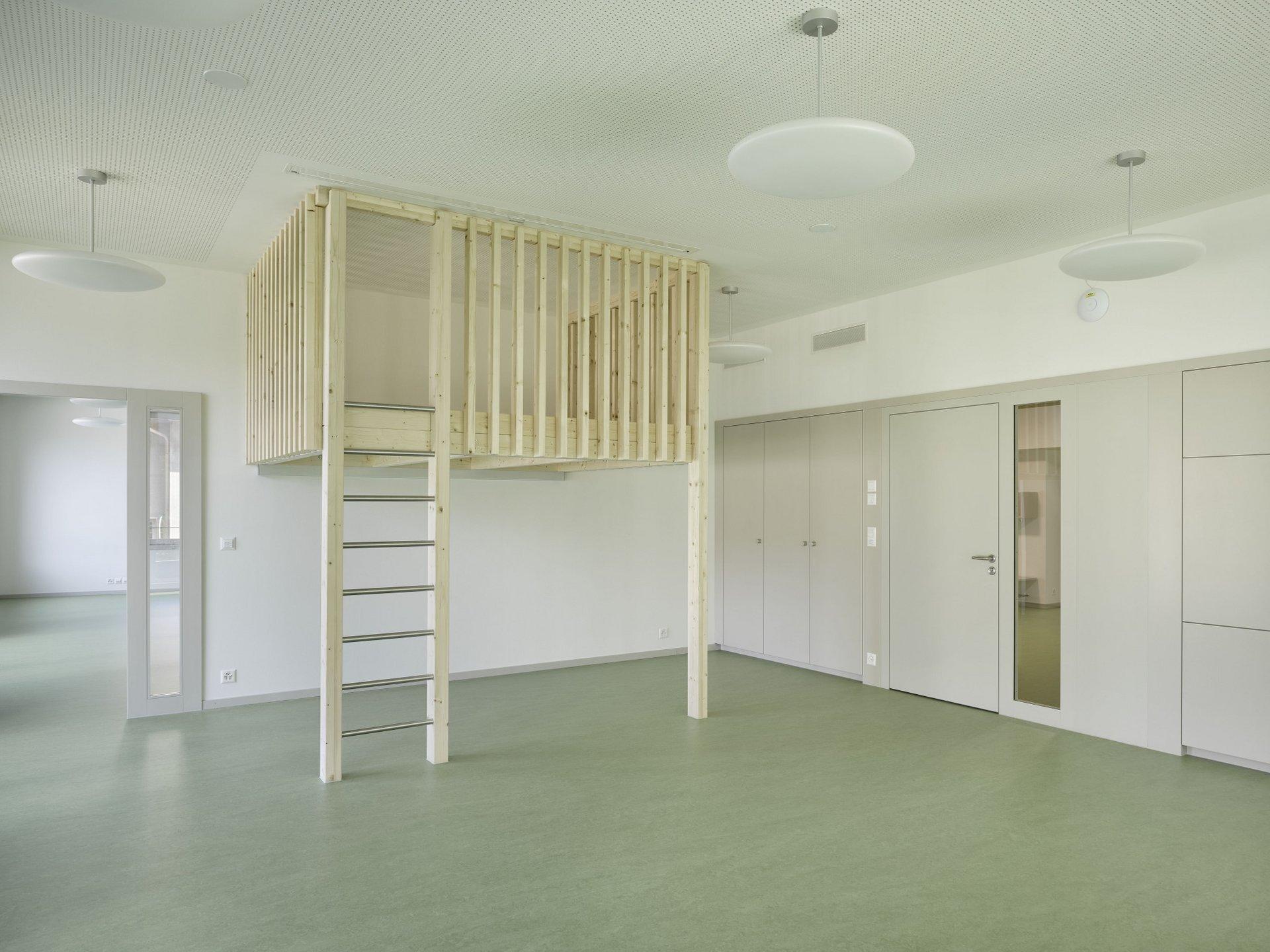 Ein Spielturm inmitten eines Klassenzimmers der über eine Leiter nach oben verfügt